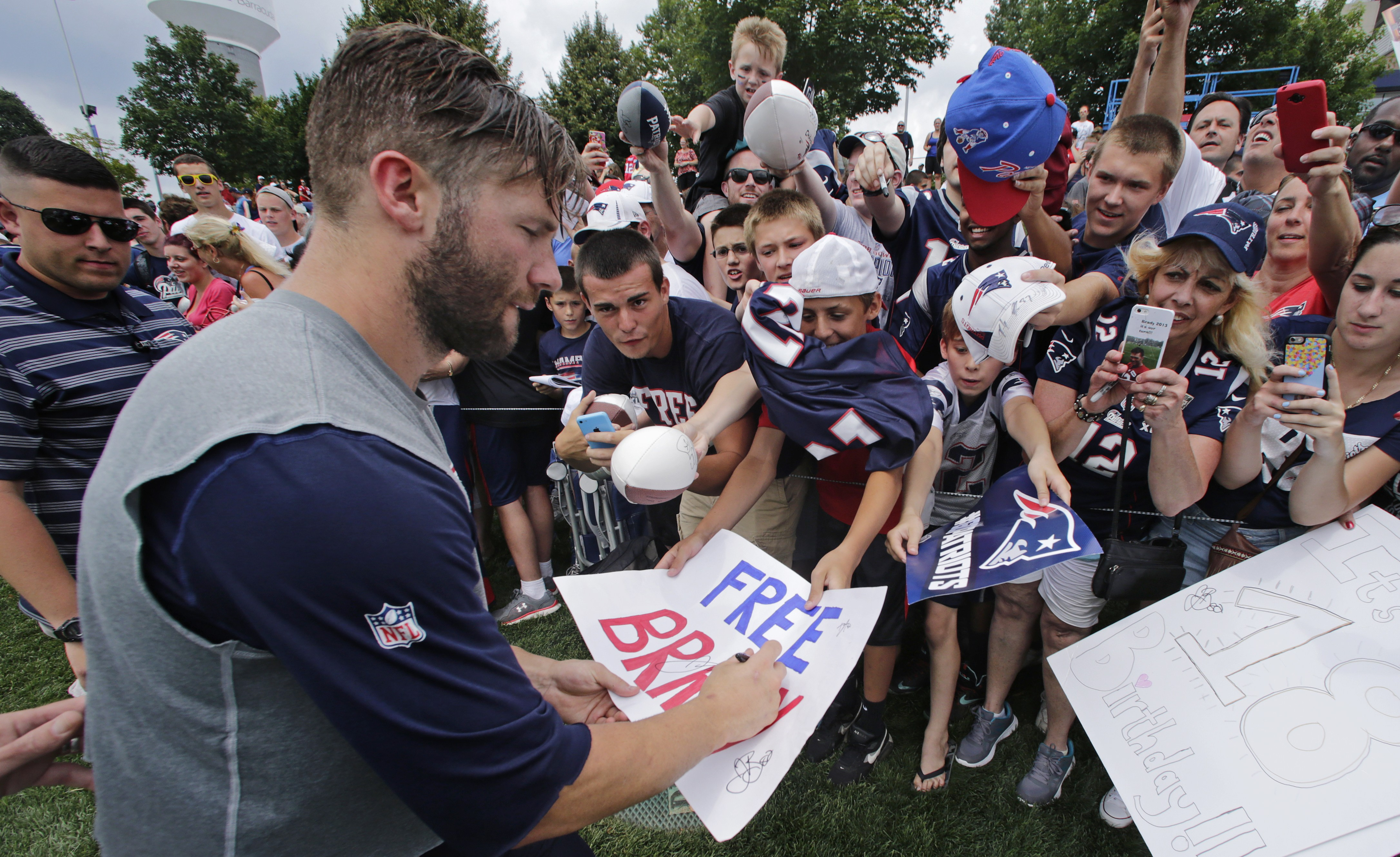 """New England Patriots wide receiver Julian Edelman signs an autograph for a fan on a """"Free Brady"""" sign during an NFL football training camp in Foxborough, Mass., Thursday, July 30, 2015. (AP Photo/Charles Krupa)"""