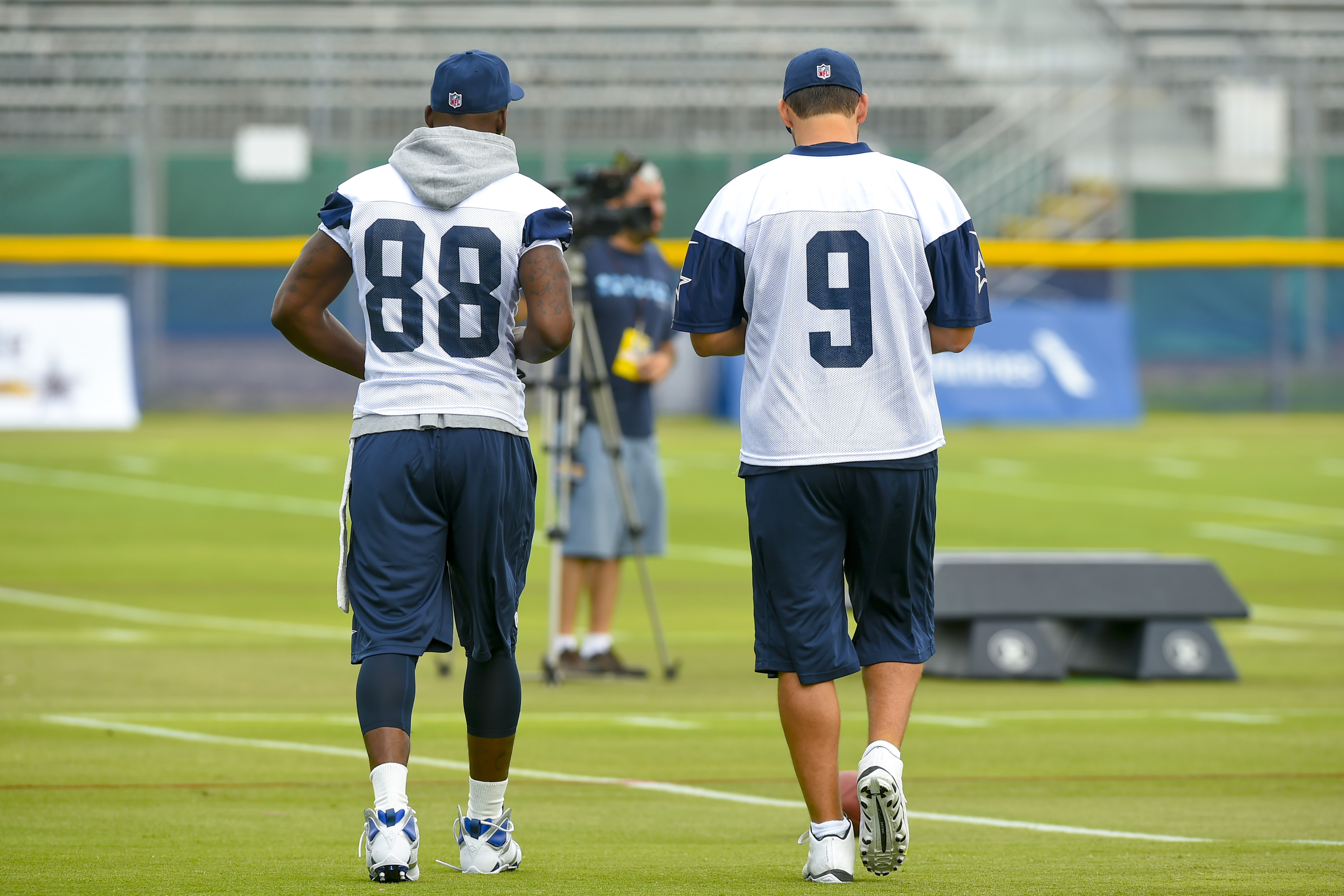 Dallas Cowboys wide receiver Dez Bryant (88) and quarterback Tony Romo (9) take the field during Dallas Cowboys NFL football training camp, Thursday, July 30, 2015, in Oxnard, Calif. (AP Photo/Gus Ruelas)