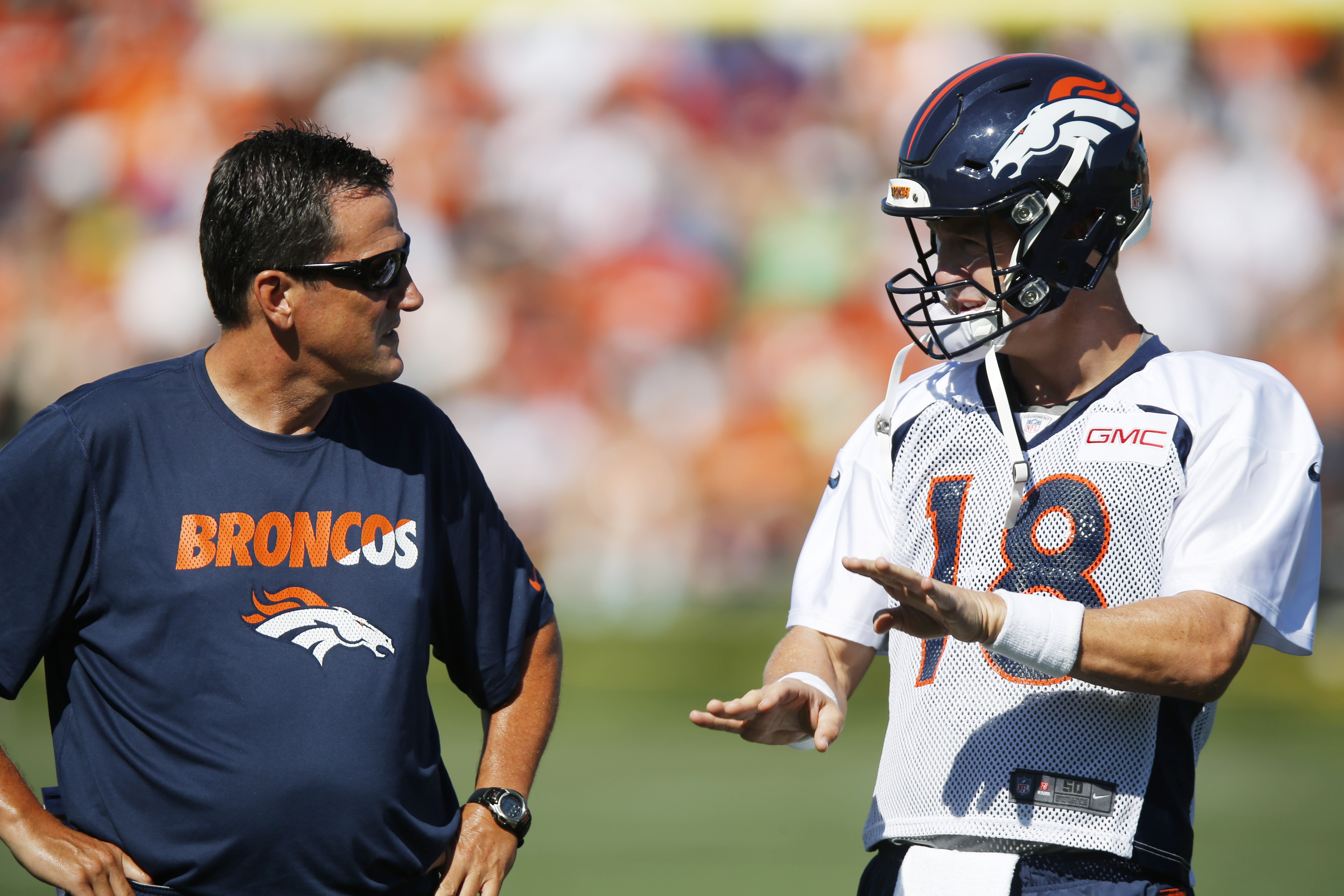 Denver Broncos quarterback Peyton Manning, right, confers with quarterbacks coach Greg Knapp at the team's NFL football training camp Friday, July 31, 2015, in Englewood, Colo. (AP Photo/David Zalubowski)