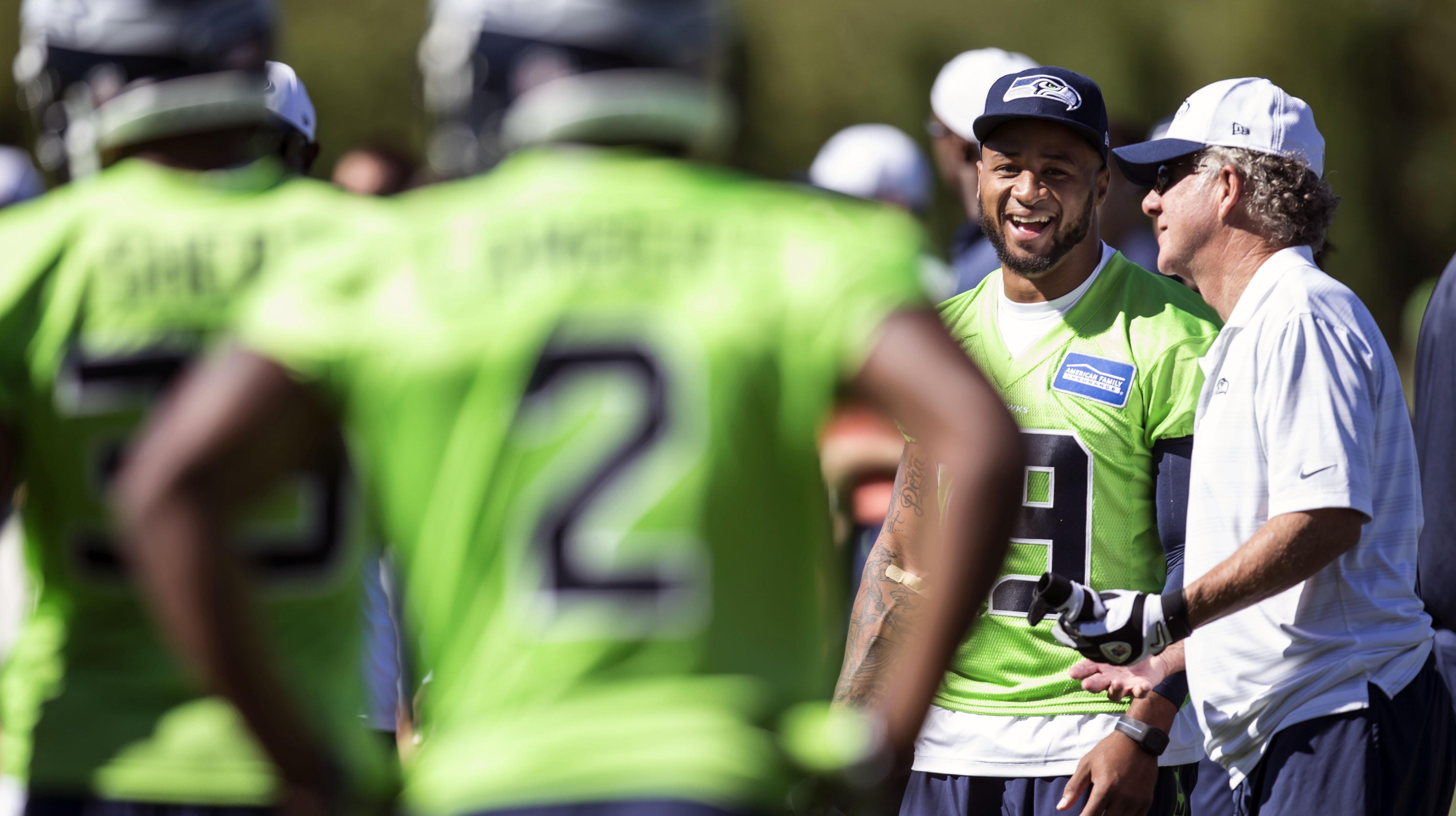 Seattle Seahawks quarterbacks coach  Carl Smith, right, talks with safety Earl Thomas, second from right, on the sidelines during an NFL football training camp on Friday, July 31, 2015, in Renton, Wash. (AP Photo/Stephen Brashear)