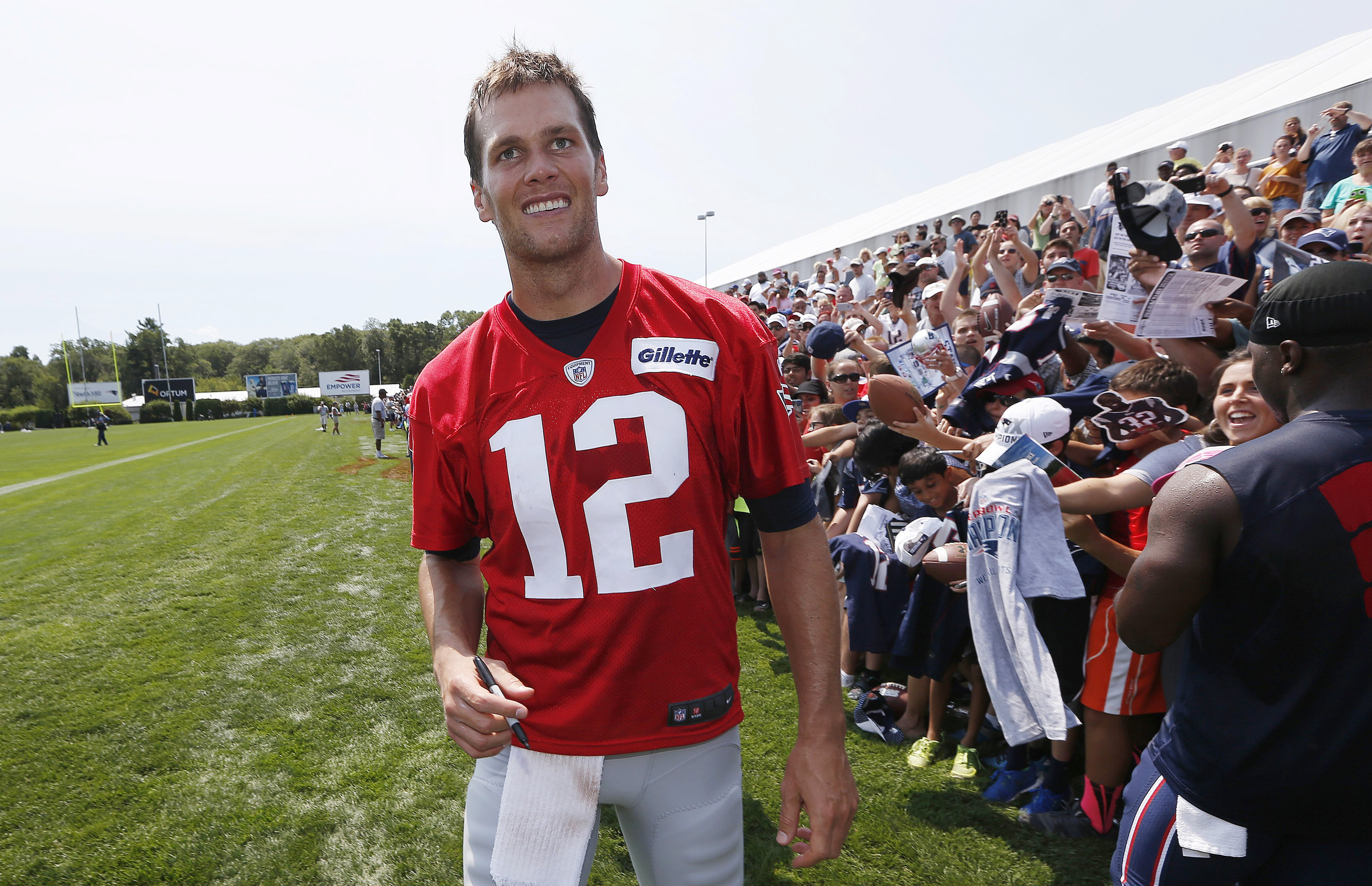 New England Patriots quarterback Tom Brady walks down the line of fans signing autographs during an NFL football training camp in Foxborough, Mass., Saturday, Aug. 1, 2015. (AP Photo/Michael Dwyer)