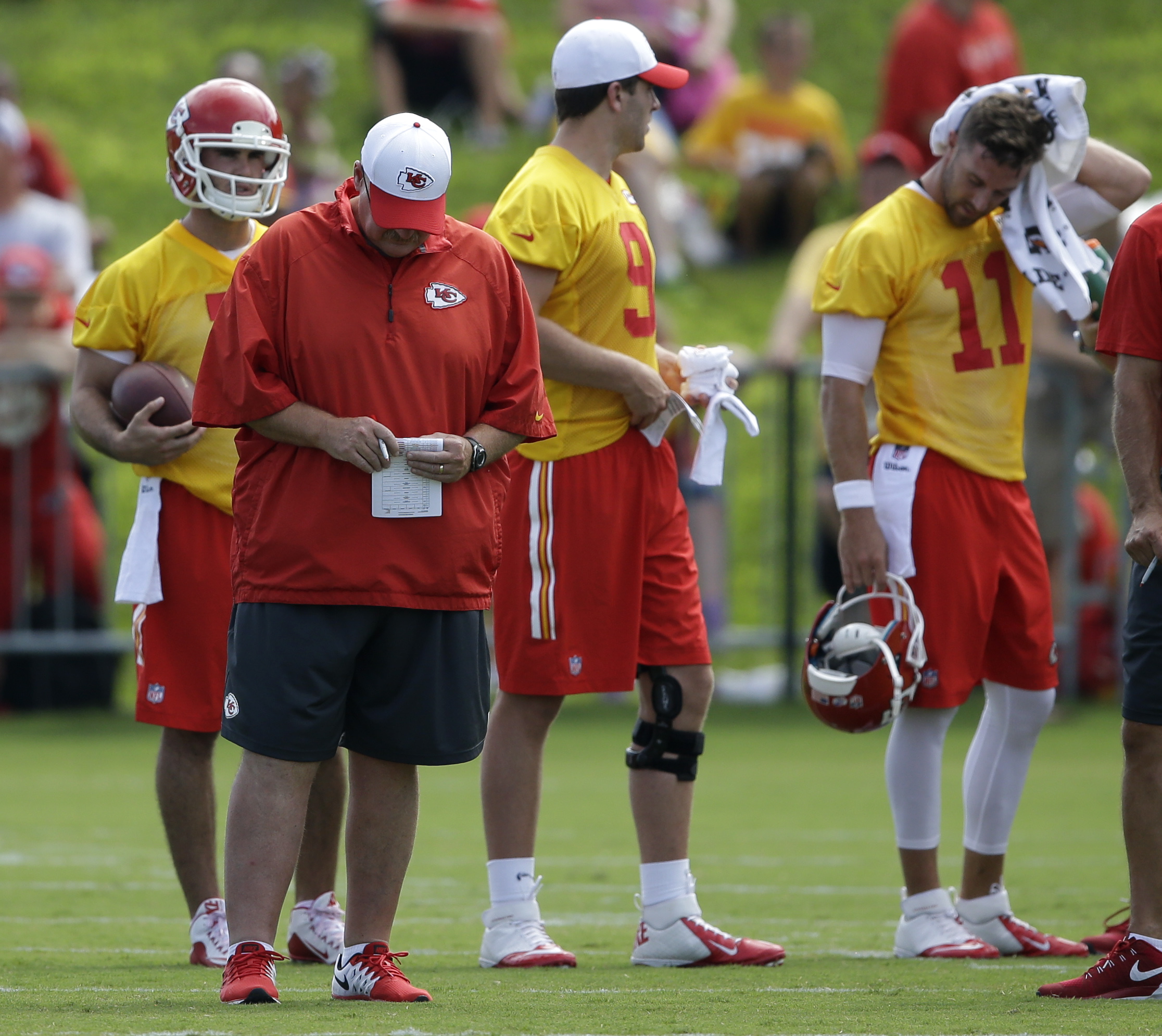 Kansas City Chiefs coach Andy Reid , front left, checks his notes in front of quarterbacks Alex Smith (11), Tyler Bray (9) and Aaron Murray, back left, during NFL football training camp in St. Joseph, Mo., Saturday, Aug. 1, 2015. (AP Photo/Orlin Wagner)