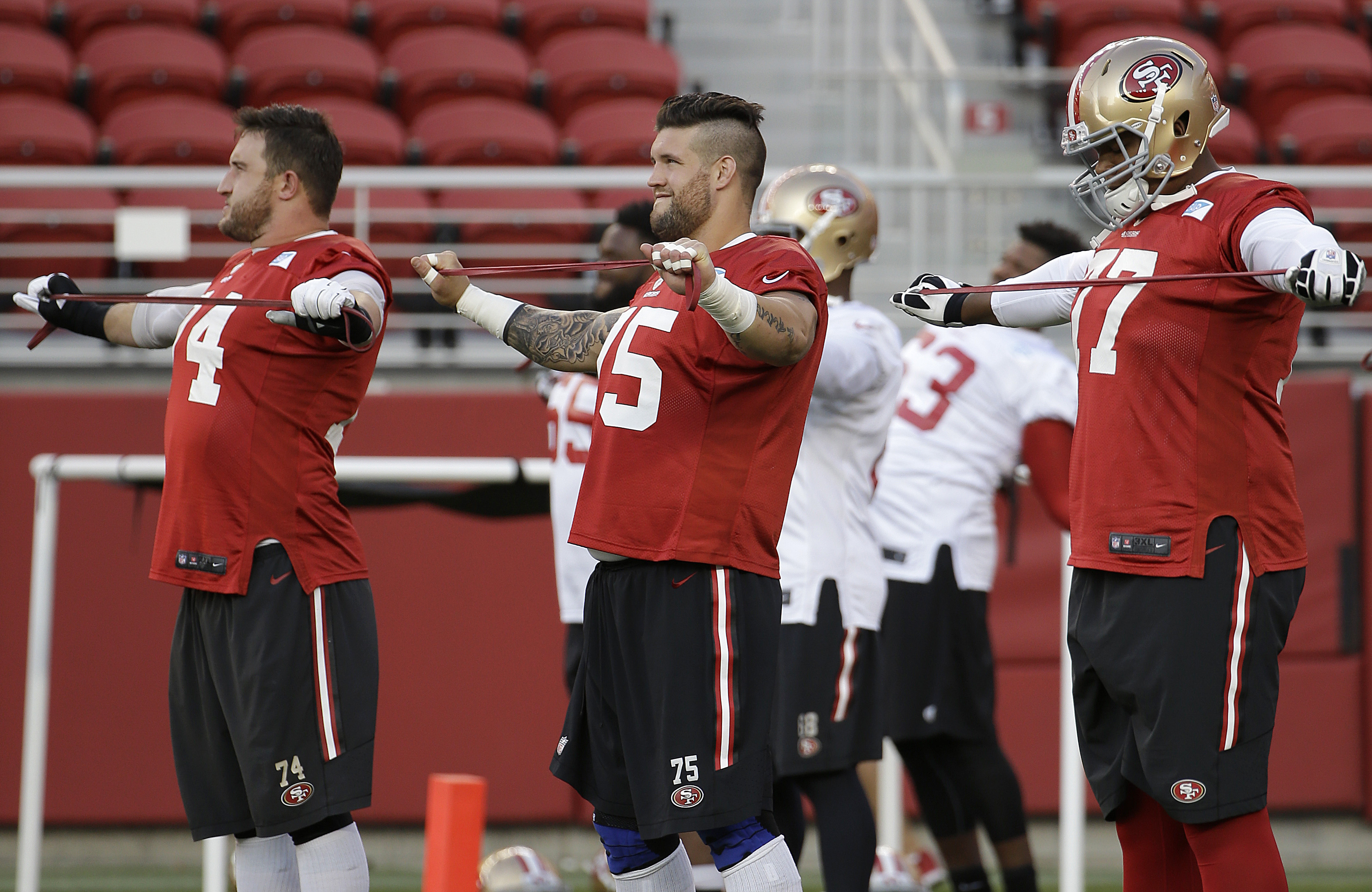 San Francisco 49ers offensive linemen Joe Staley, from left, Alex Boone and Trent Brown stretch during the team's NFL football training camp in Santa Clara, Calif., Saturday, Aug. 1, 2015. (AP Photo/Jeff Chiu)