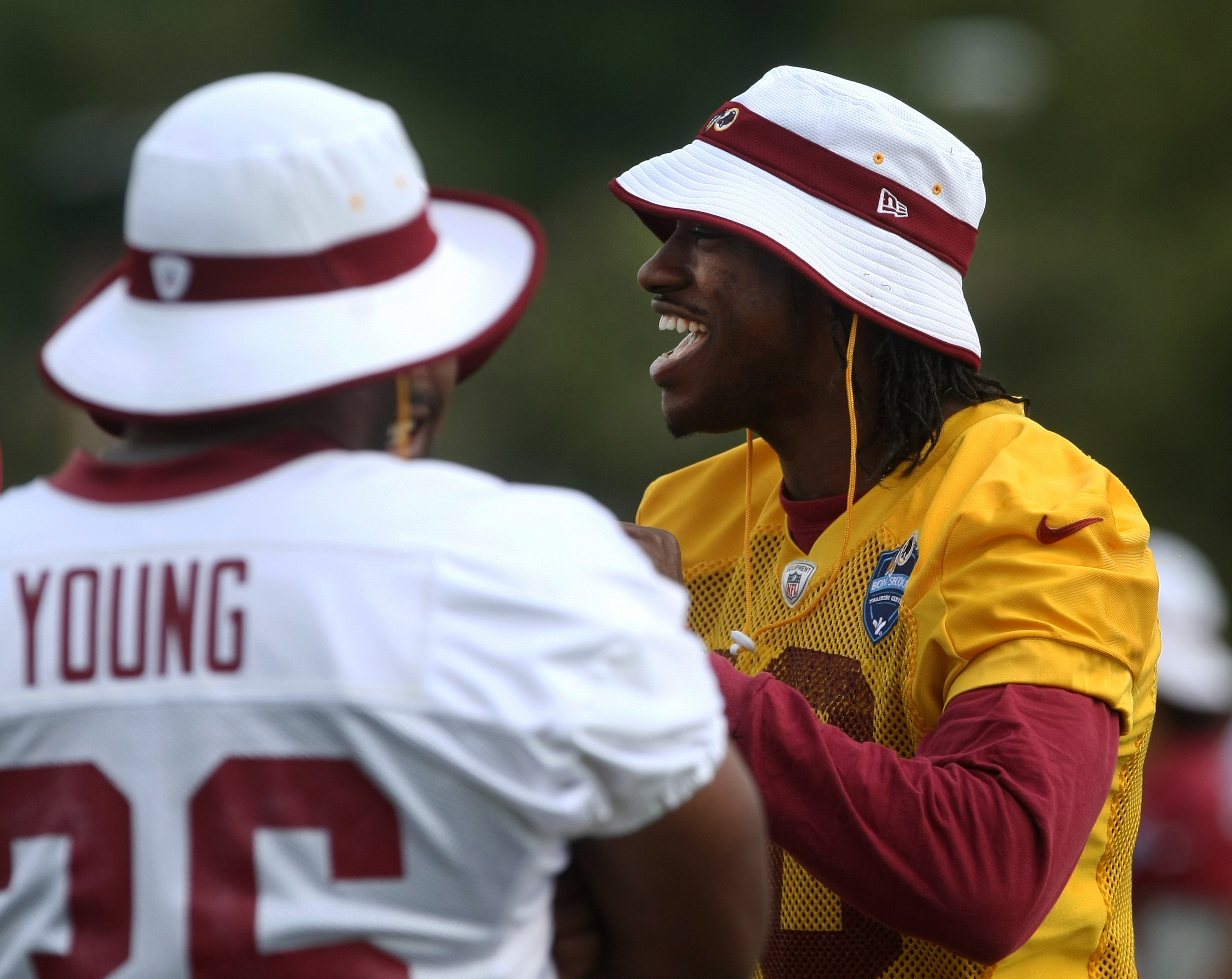 Washington Redskins quarterback Robert Griffin III, right, laughs with Washington Redskins fullback Darrel Young during the team's NFL football training camp in Richmond, Va., Monday, Aug. 3, 2015.   (AP Photo/Jason Hirschfeld)