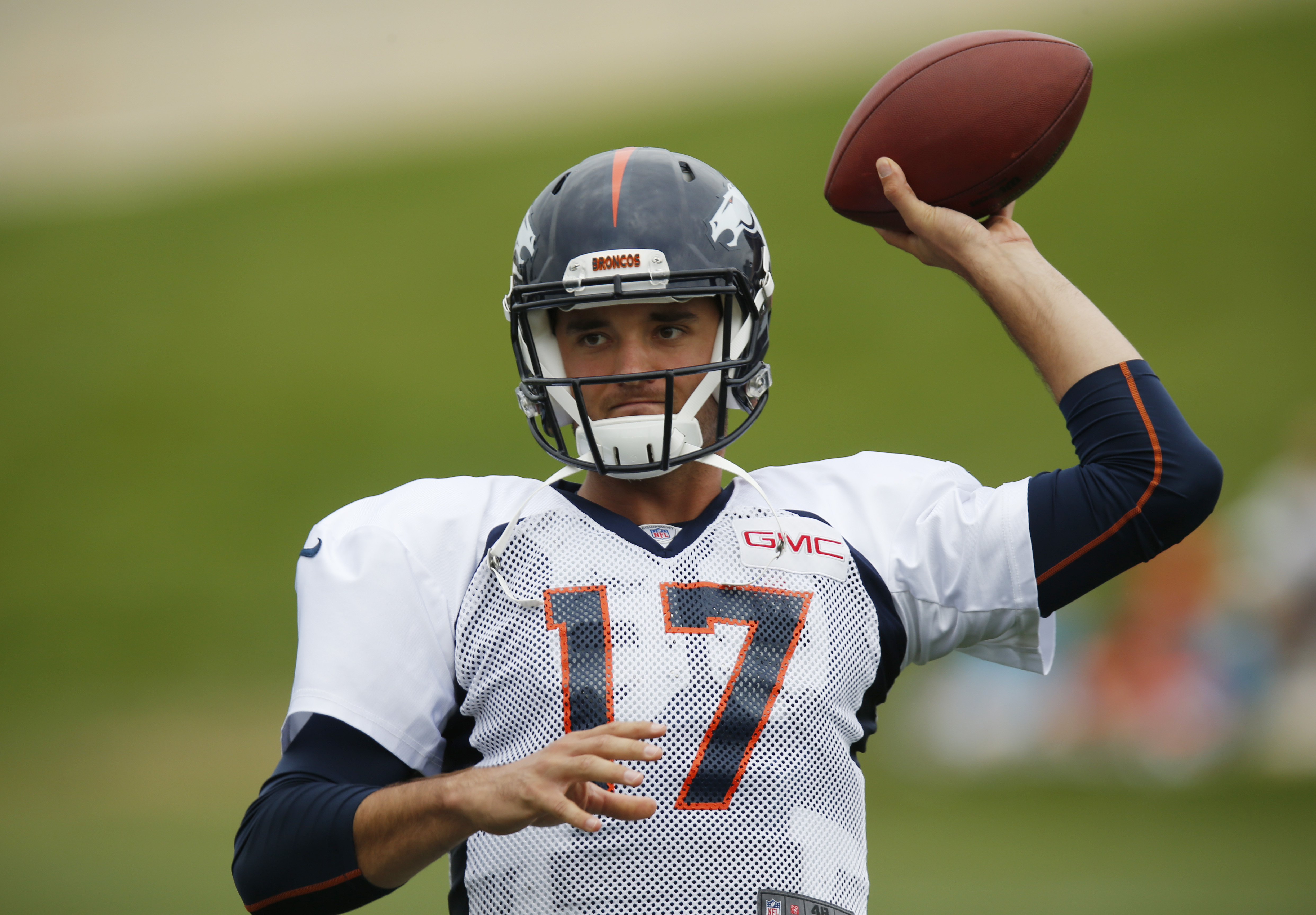 Denver Broncos quarterback Brock Osweiler, who is a right-handed passer, jokes with teammates by using his left hand to throw the ball at the team's NFL football training camp Monday, Aug. 3, 2015, in Englewood, Colo. (AP Photo/David Zalubowski)