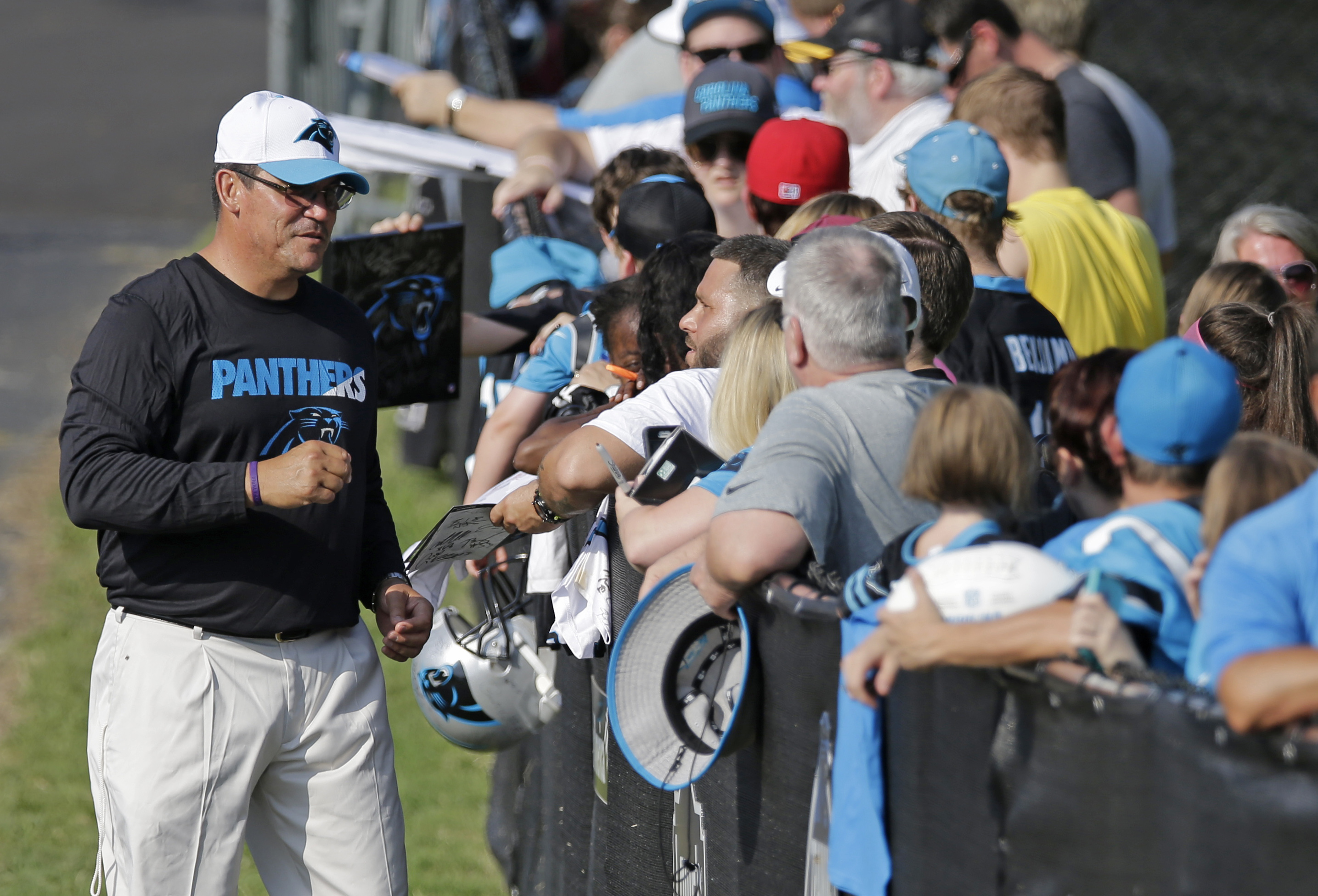 Carolina Panthers head coach Ron Rivera, left, signs autographs for fans as he arrives for the NFL football team's training camp in Spartanburg, S.C., Monday, Aug. 3, 2015. (AP Photo/Chuck Burton)