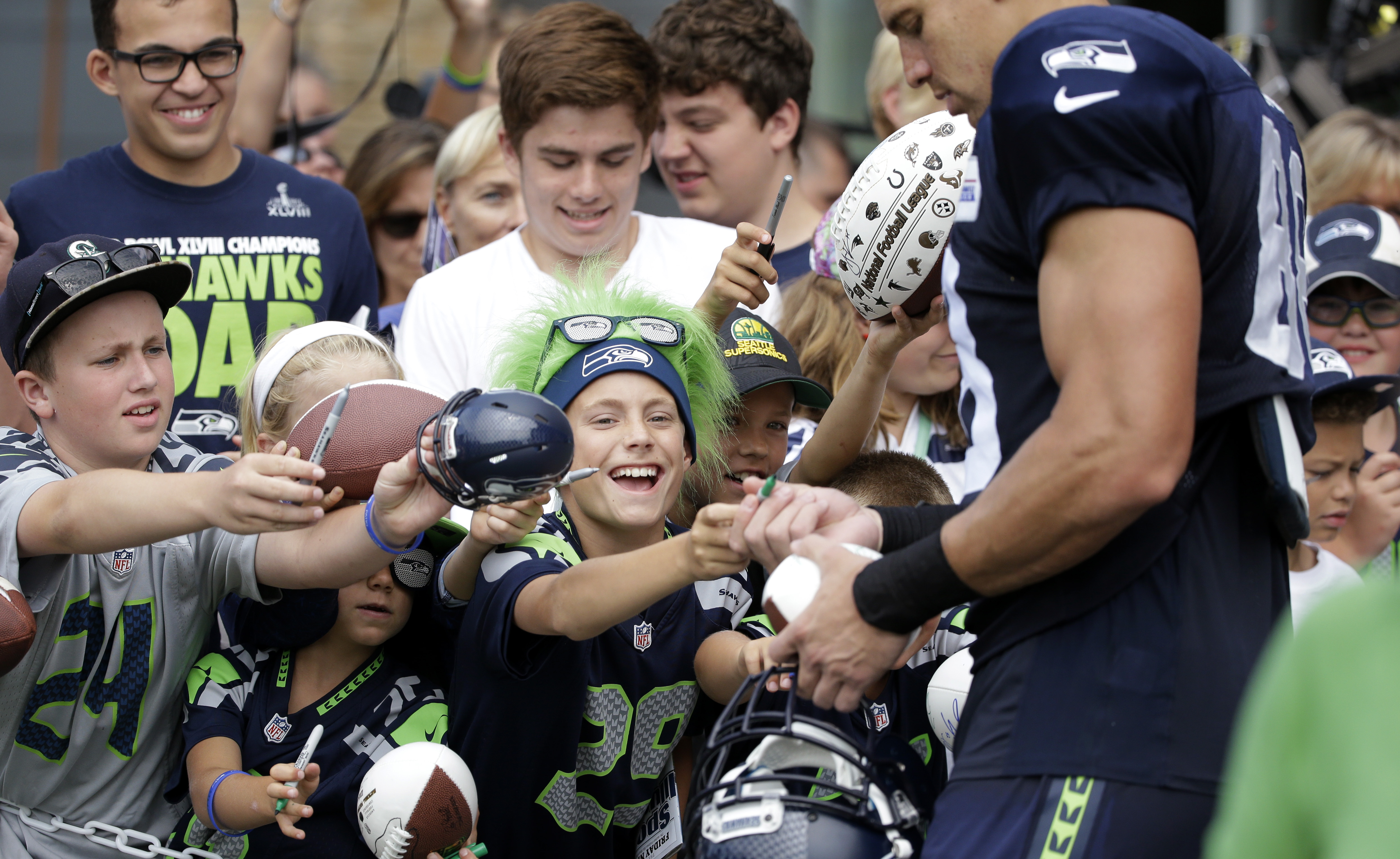 Seattle Seahawks fans reach toward Jimmy Graham for an autograph after an NFL football training camp Monday, Aug. 3, 2015, in Renton, Wash. (AP Photo/Elaine Thompson)