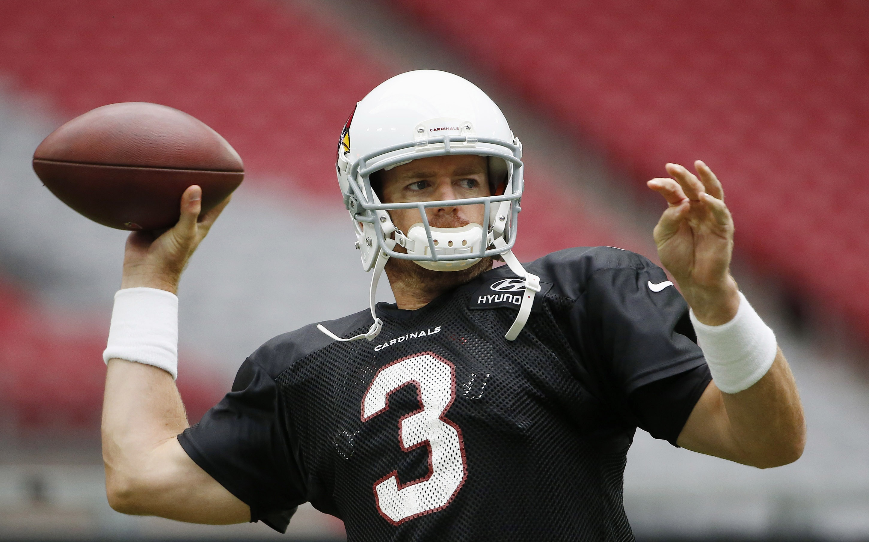 Arizona Cardinals' Carson Palmer throws a pass as he warms up during an NFL football training camp practice, Monday, Aug. 3, 2015, in Glendale, Ariz. (AP Photo/Ross D. Franklin)