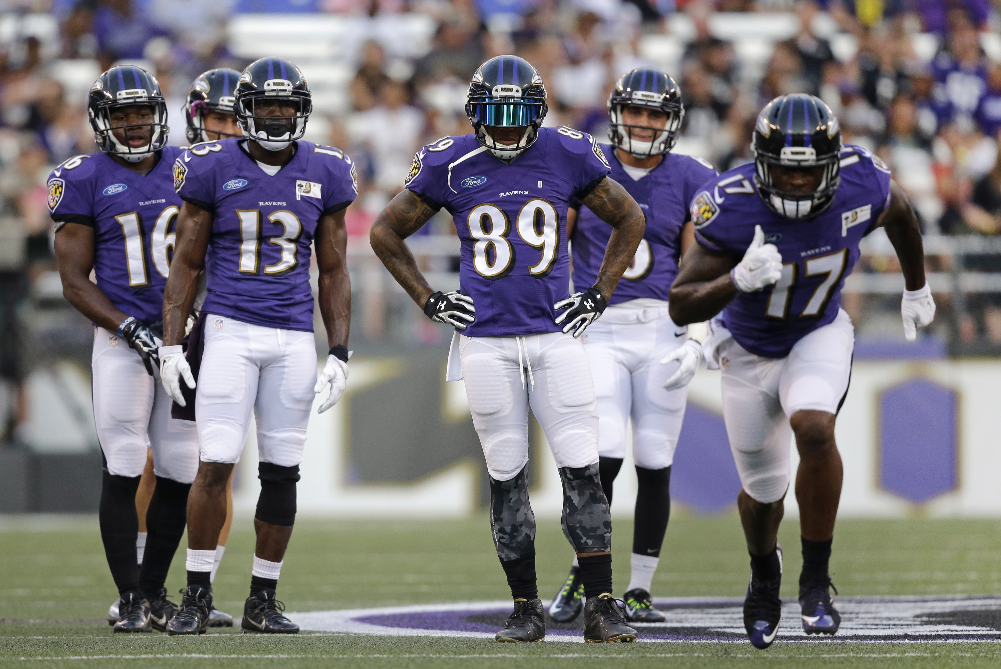 Baltimore Ravens wide receiver Steve Smith, center, stands alongside teammates as fellow wide receiver Jeremy Butler (17) runs a rout during NFL football training camp, Monday, Aug. 3, 2015, in Baltimore. (AP Photo/Patrick Semansky)