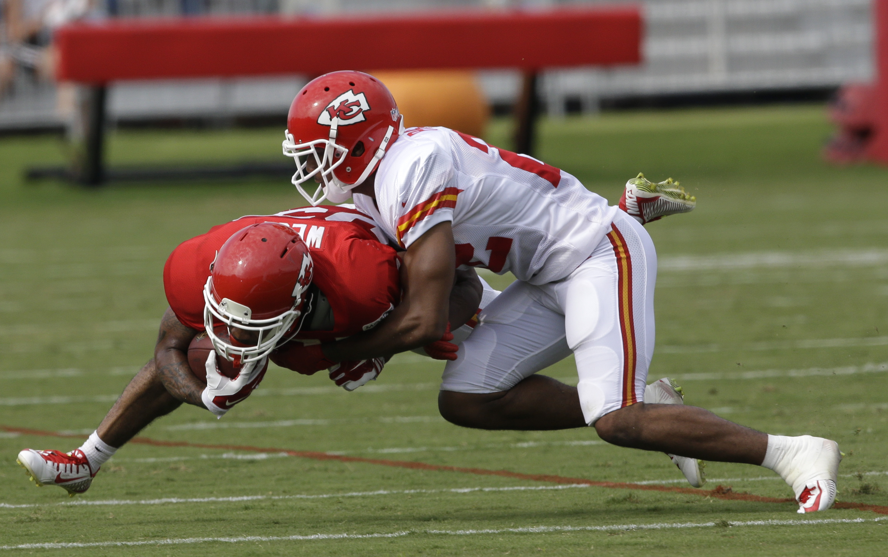 Kansas City Chiefs running back Charcandrick West (35) is tackled by cornerback Marcus Peters, right, during NFL football training camp in St. Joseph, Mo., Tuesday, Aug. 4, 2015. (AP Photo/Orlin Wagner)
