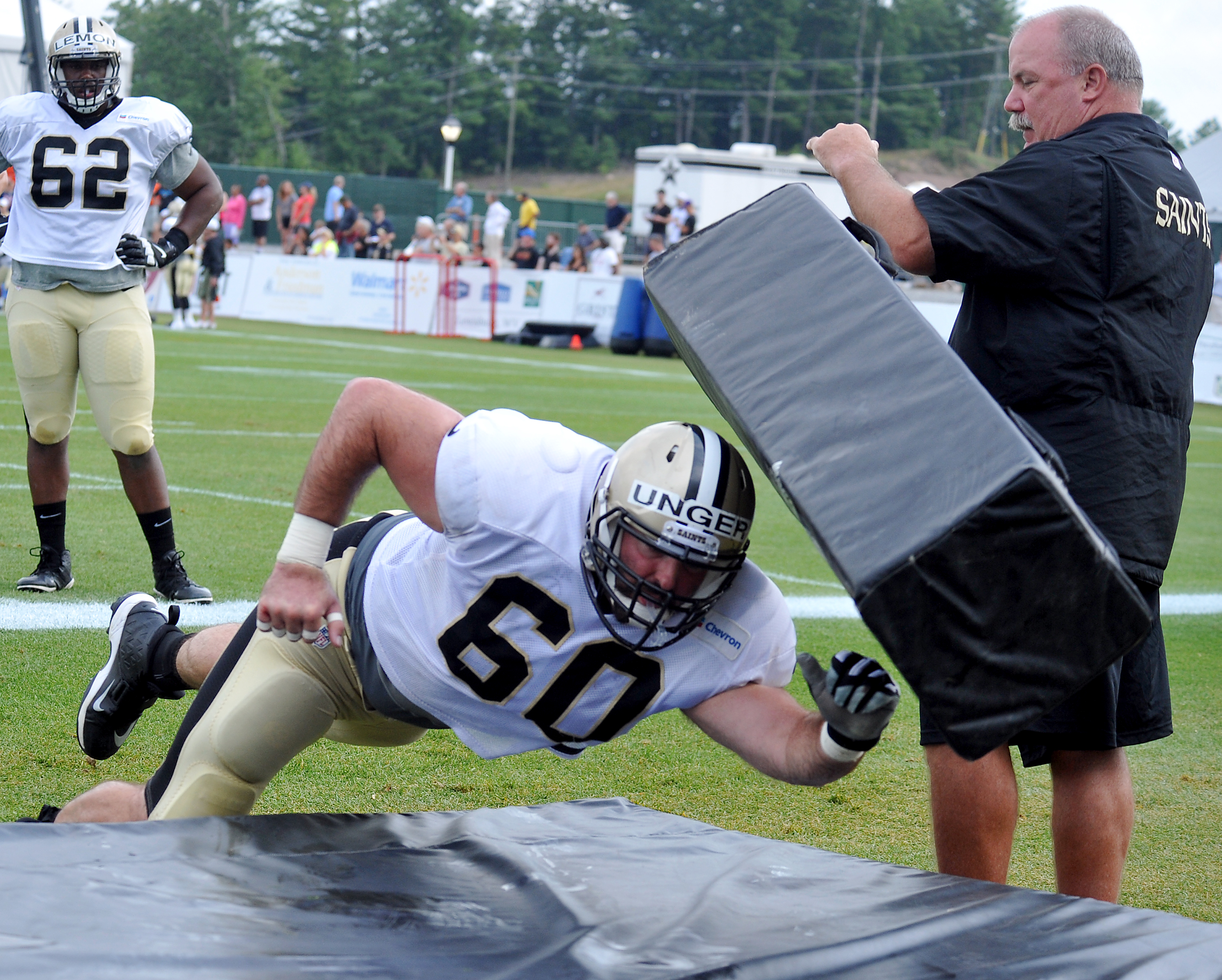 New Orleans Saints center Max Unger (60) hits a mat during a drill at the team's NFL football training camp in White Sulphur Springs, W. Va., Wednesday, Aug. 5, 2015. (AP Photo/Chris Tilley)