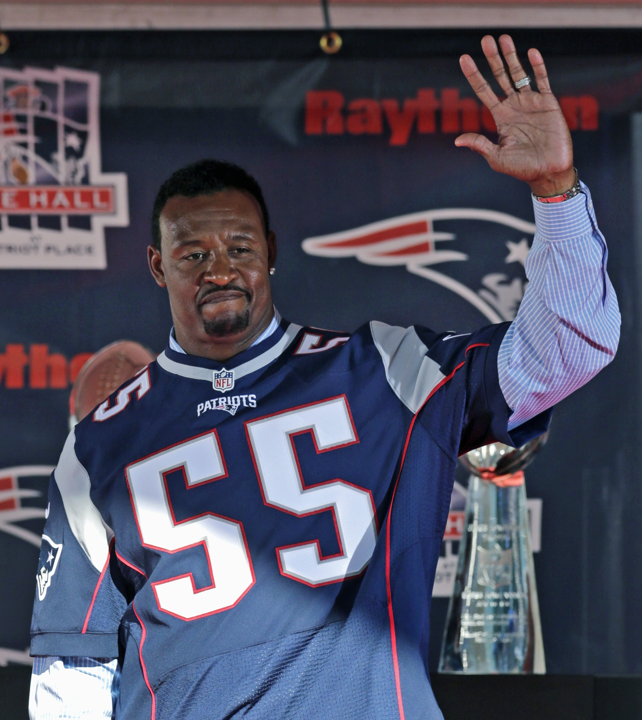 Former New England Patriots linebacker Willie McGinest acknowledges fans as he is inducted into the Patriot's Hall of Fame prior to an NFL football training camp in Foxborough, Mass., Wednesday, Aug. 5, 2015. (AP Photo/Charles Krupa)