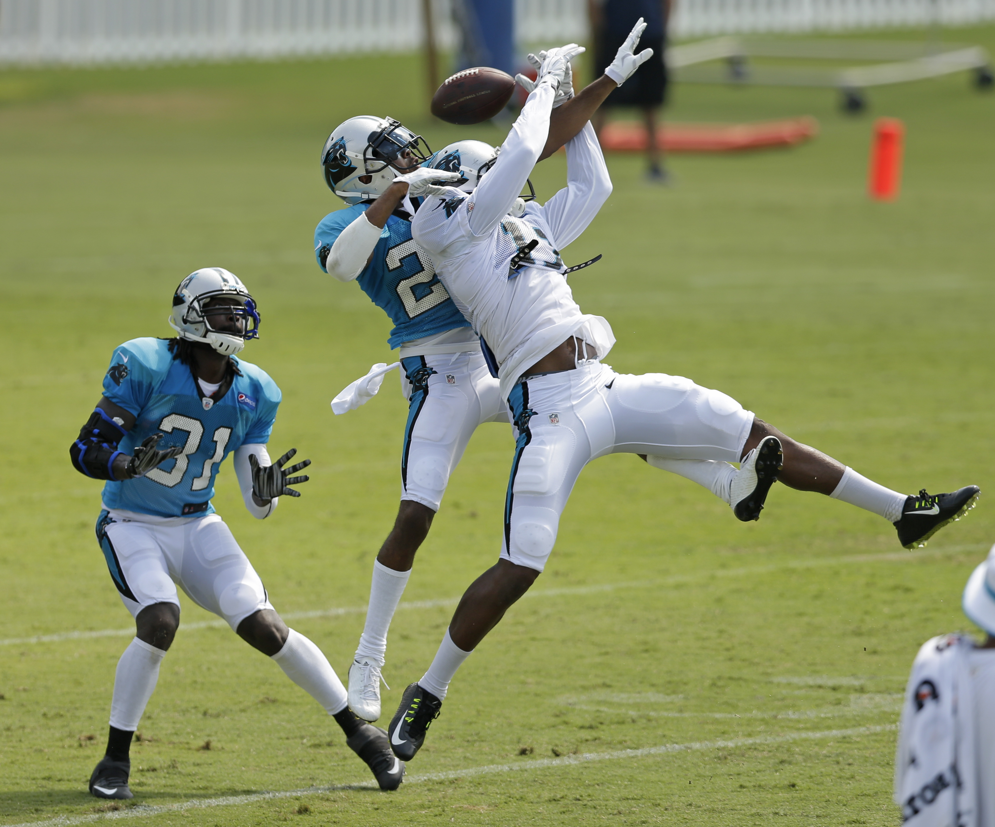 In this photo taken Aug. 3, 2015,  Carolina Panthers' Charles Tillman, left, watches as Carolina Panthers' Devin Funchess, right, and Josh Norman, center, battle for the ball during the NFL football team's training camp in Spartanburg, S.C., Monday, Aug.