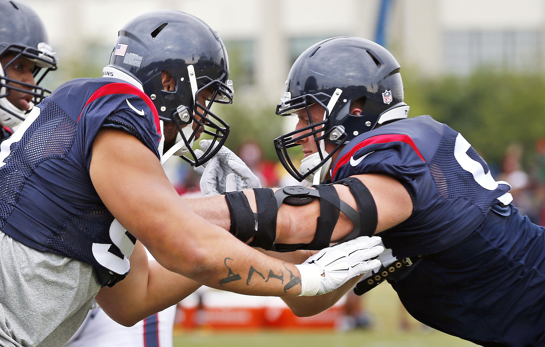 Houston Texans' Tevita Finau, left, and J.J. Watt run drills during NFL training camp Thursday, Aug. 6, 2015, in Richmond, Va.  (Alexa Welch Edlund/Richmond Times-Dispatch via AP) MANDATORY CREDIT