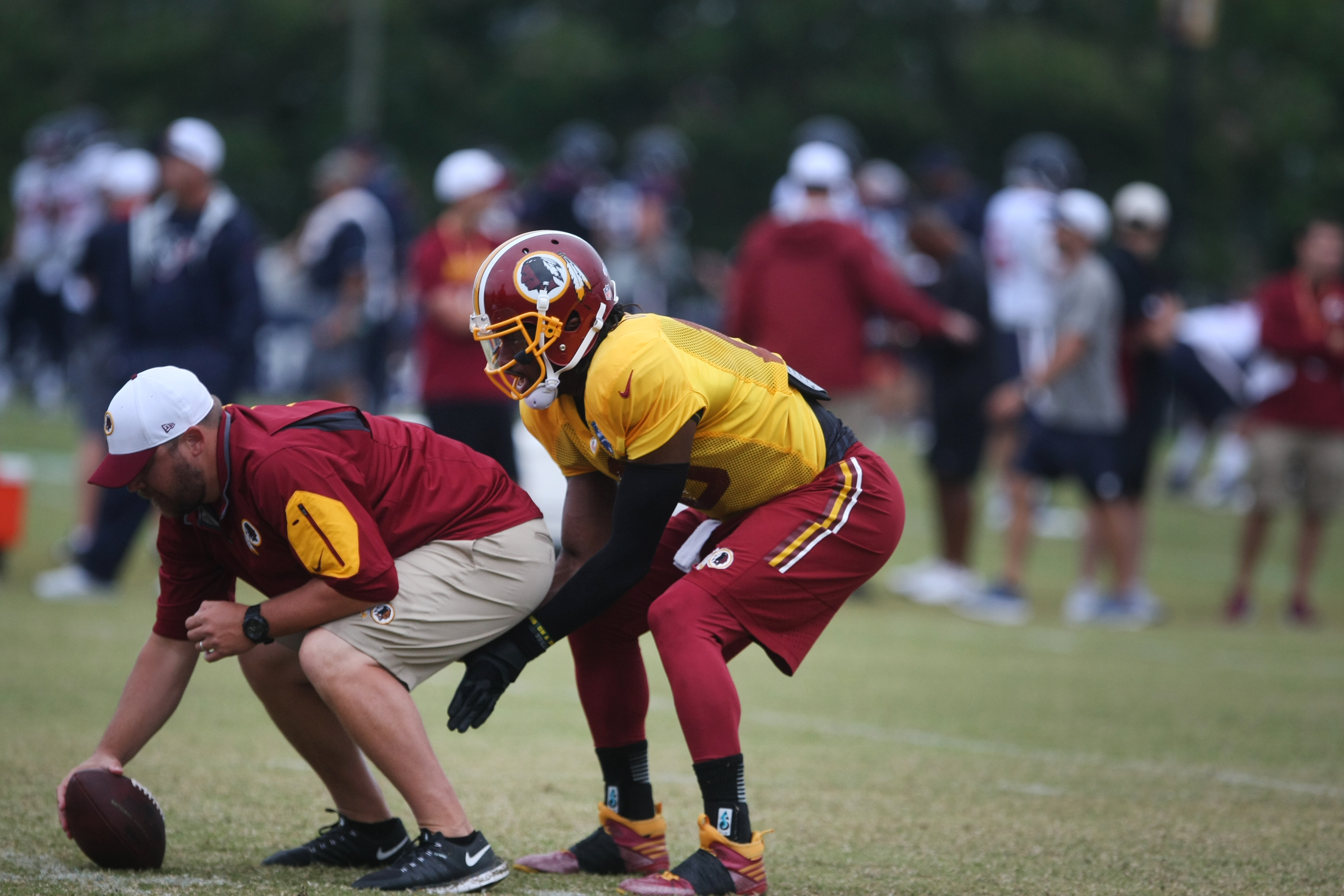 Washington Redskins quarterback Robert Griffin III takes a snap during a joint NFL training camp with the Houston Texans in Richmond, Va., Friday, Aug. 7, 2015.   (AP Photo/Jason Hirschfeld)