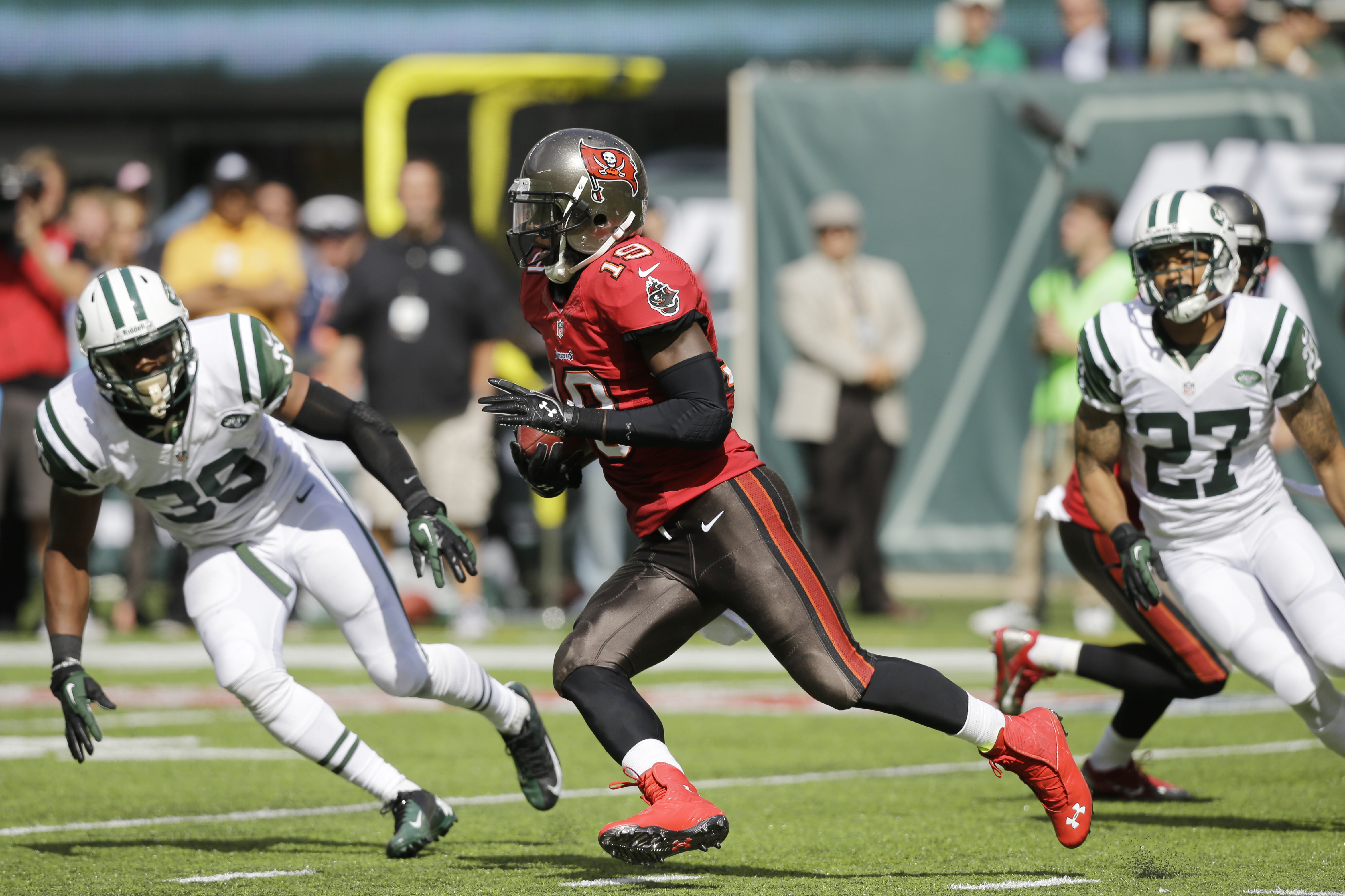 Tampa Bay Buccaneers wide receiver Mike Williams, center, runs with the ball as New York Jets strong safety Antonio Allen (39) and cornerback Dee Milliner (27) defend in the second half of an NFL football game, Sunday, Sept. 8, 2013, in East Rutherford, N