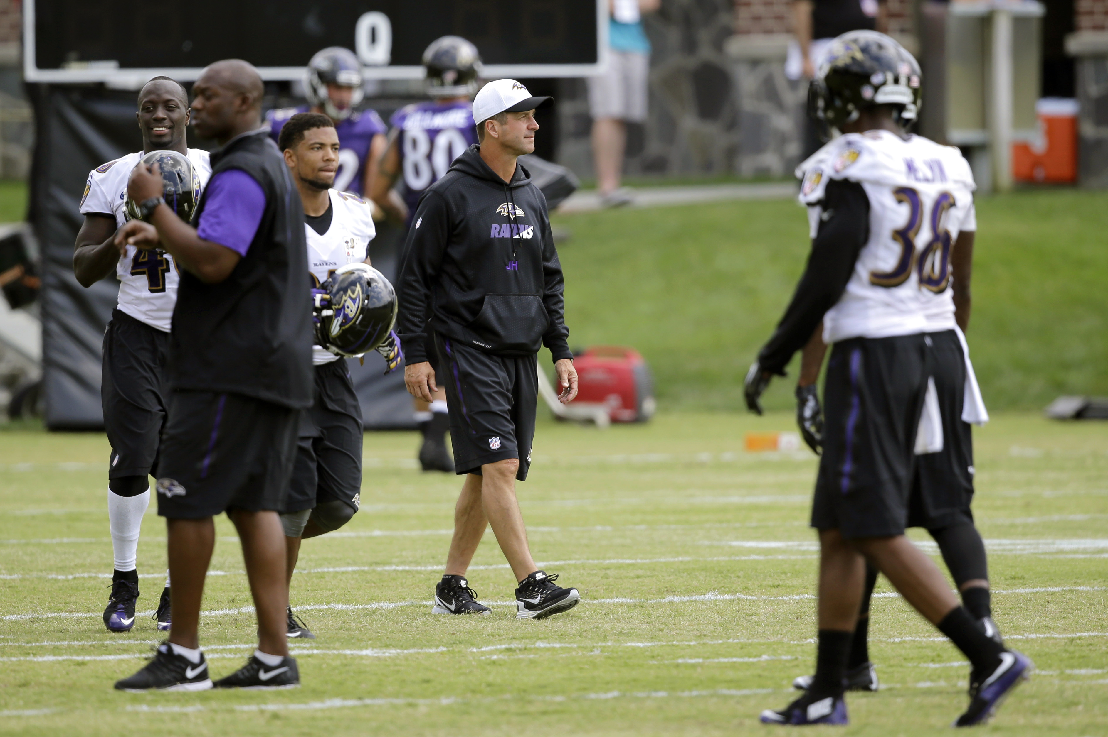 Baltimore Ravens head coach John Harbaugh, center, walks on the field during NFL football training camp, Friday, Aug. 7, 2015, in Owings Mills, Md. (AP Photo/Patrick Semansky)