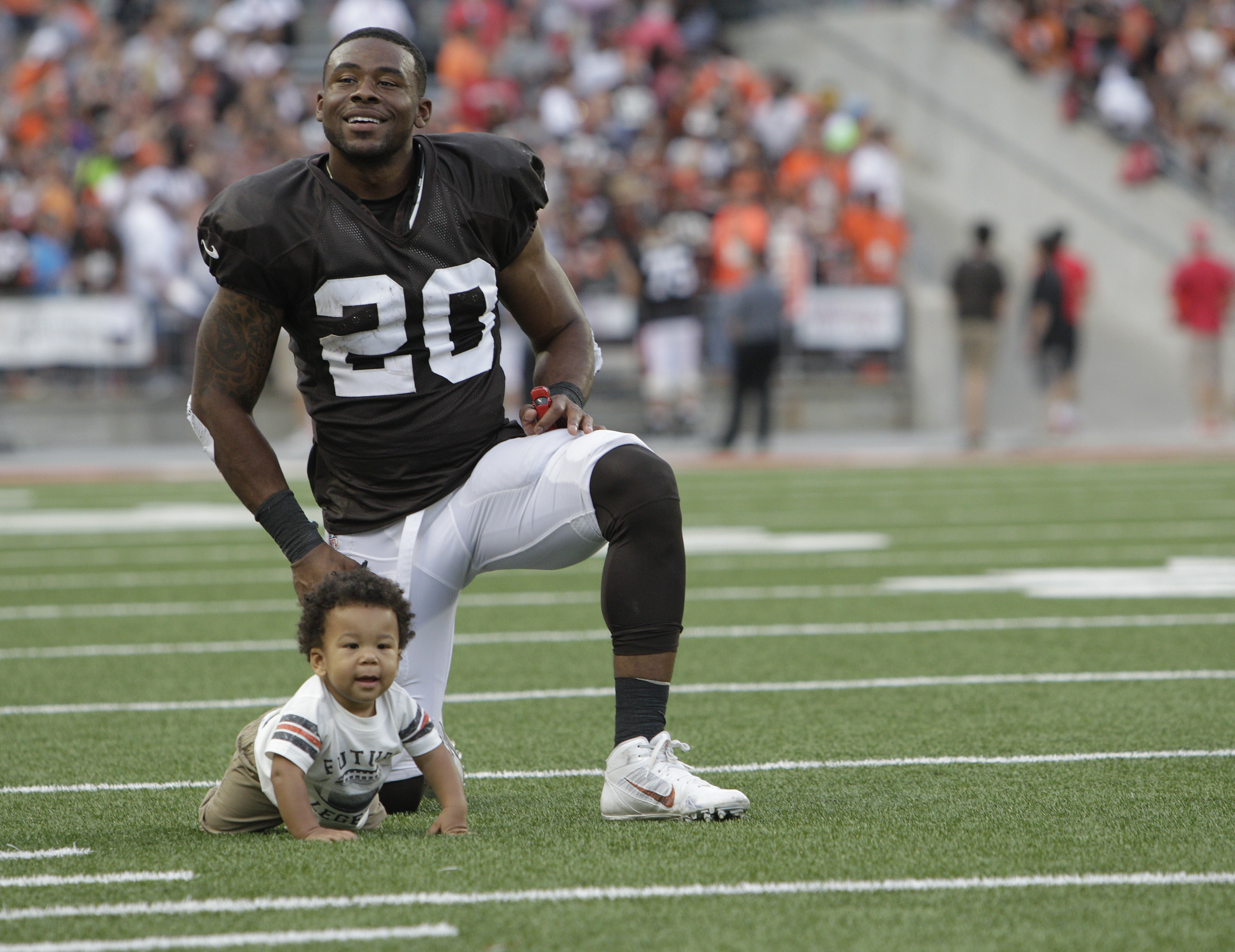 Cleveland Browns running back Shaun Draughn watches his son Kamden crawl on the field at Ohio Stadium after an NFL football training camp scrimmage game at Ohio Stadium, Friday, Aug. 7, 2015, in Columbus, Ohio. (AP Photo/Jay LaPrete)