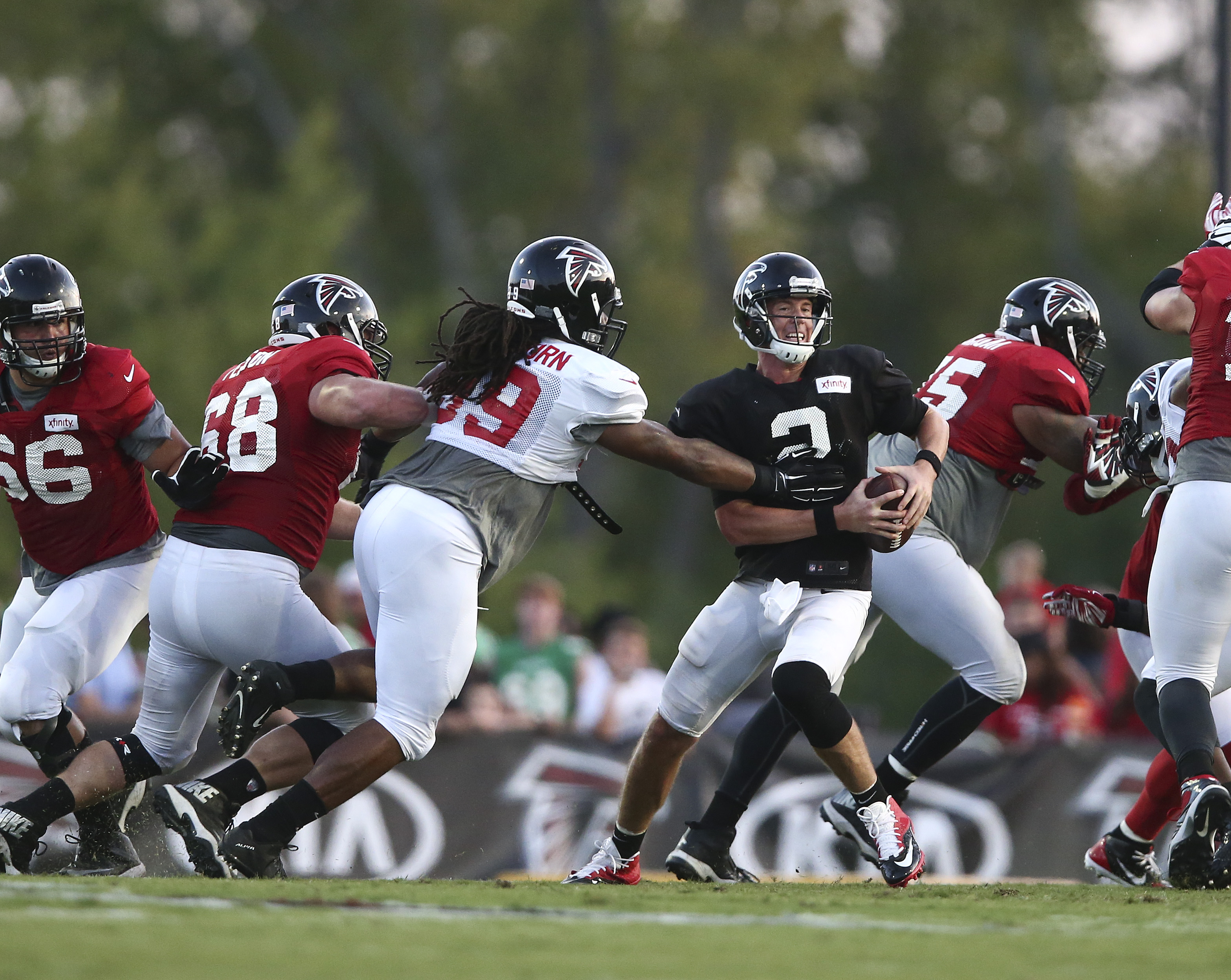 "Atlanta Falcons defensive end Adrian Clayborn (99) gets a hand on quarterback Matt Ryan during the the team's annual ""Friday Night Lights"" NFL football practice Friday, Aug. 7, 2015, in Buford, Ga. (AP Photo/John Bazemore)"