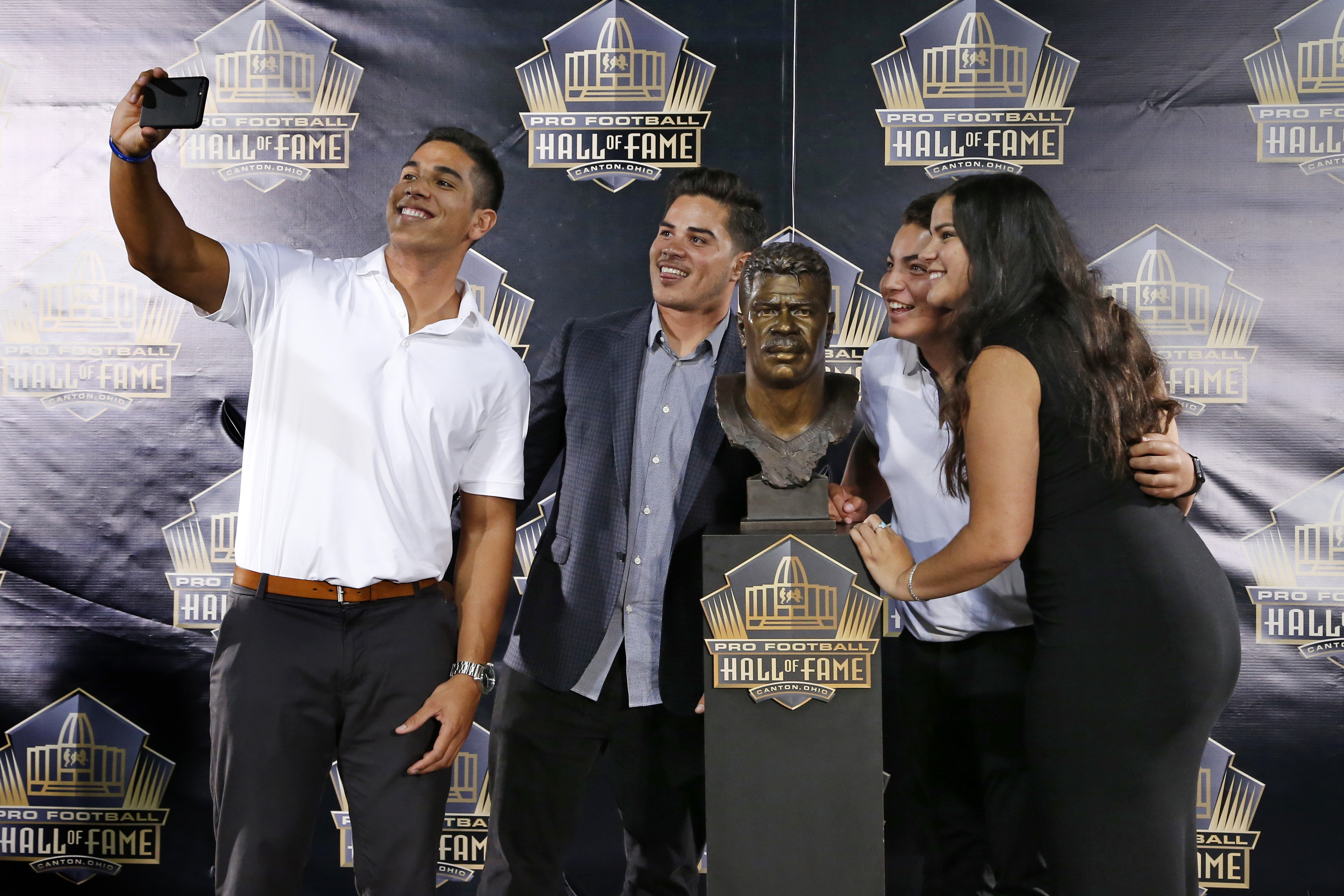 Children of former NFL player Junior Seau, from left, Jake, Tyler, Hunter and Sydney pose for a selfie with the bust of their late father, during inductions at the Pro Football Hall of Fame on Saturday, Aug. 8, 2015, in Canton, Ohio.  (AP Photo/Gene J. Pu