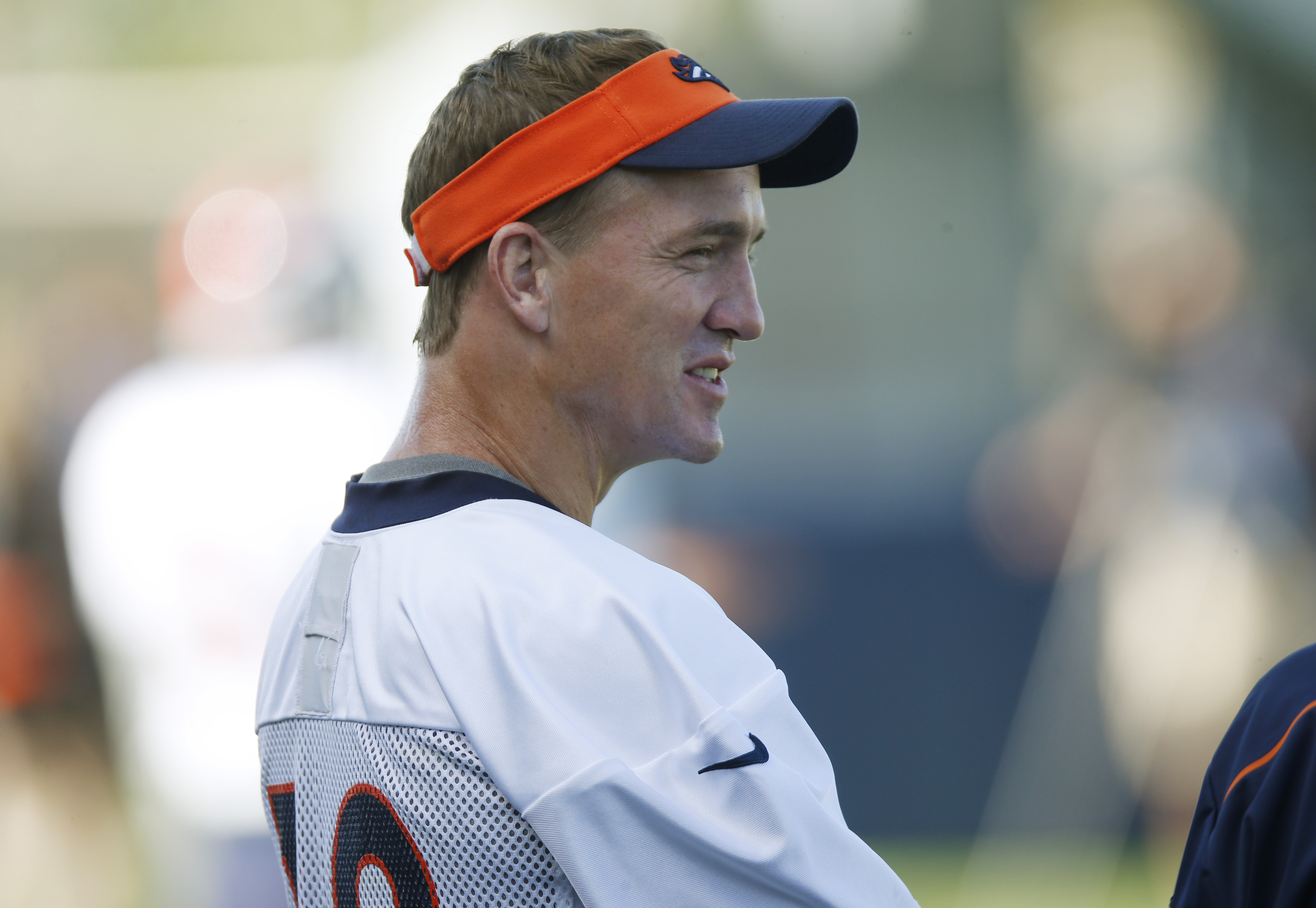Denver Broncos quarterback Peyton Manning jokes with coaches as he looks on during a morning session at the team's NFL training camp Sunday, Aug. 9, 2015, in Englewood, Colo. (AP Photo/David Zalubowski)