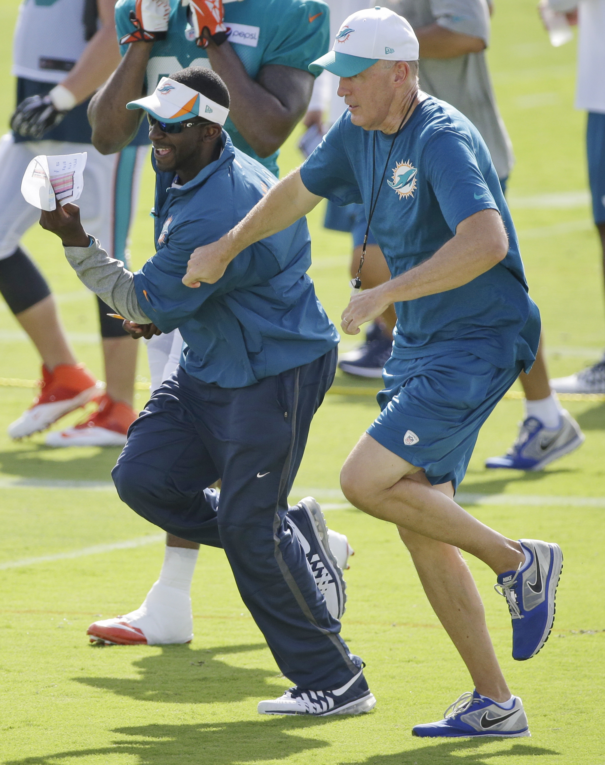 In this Wednesday, Aug. 5, 2015, photo, Miami Dolphins head coach Joe Philbin, foreground, races assistant defensive backs coach Blue Adams as they change practice fields at the teams NFL football training camp in Davie, Fla. Philbin has been described as