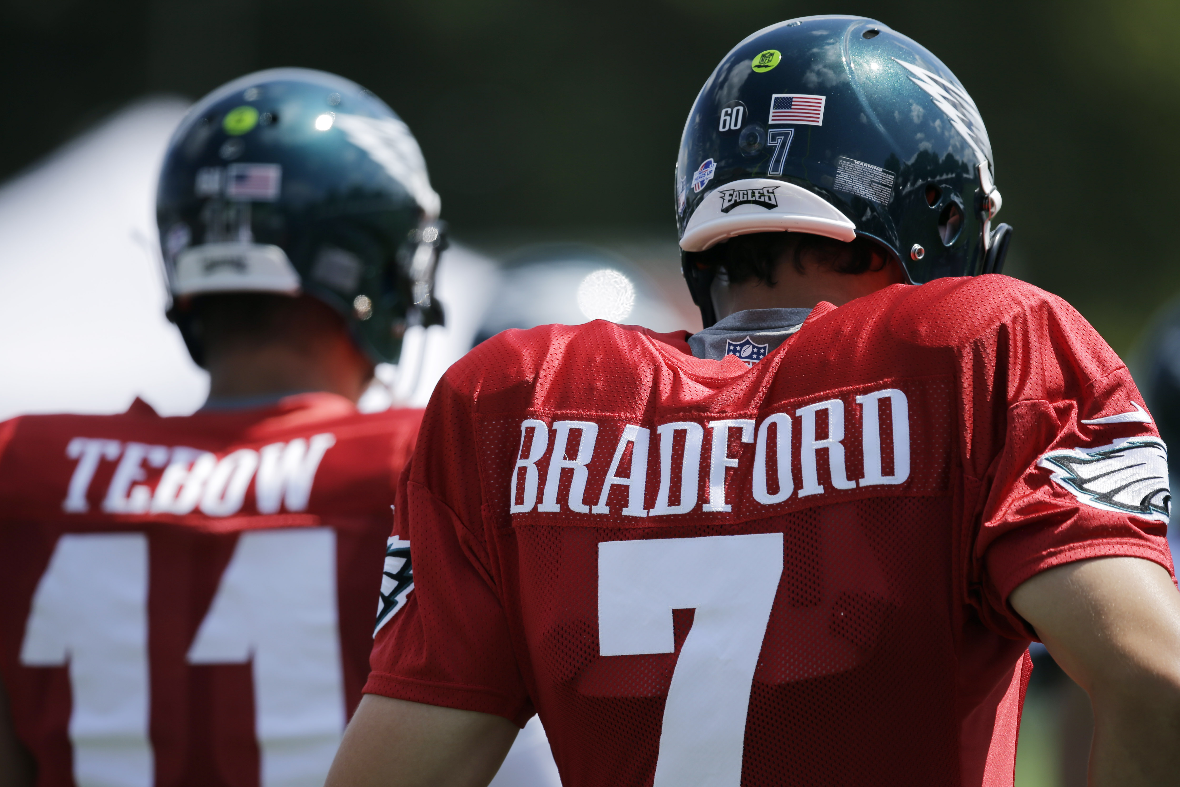Philadelphia Eagles quarterbacks Sam Bradford, right, and Tim Tebow pause during warm ups before practice at NFL football training camp, Wednesday, Aug. 12, 2015, in Philadelphia. (AP Photo/Matt Slocum)