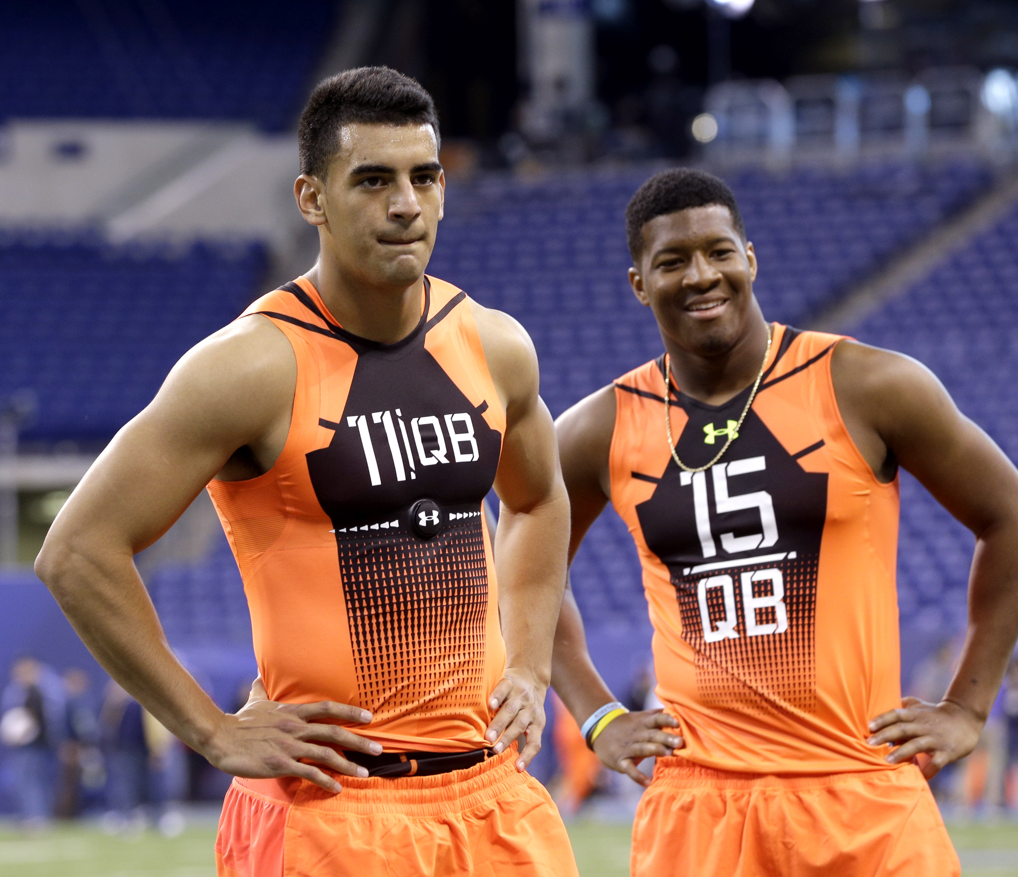 FILE - In this Feb. 21, 2015, file photo, then-Oregon quarterback Marcus Mariota (11) and then-Florida State quarterback Jameis Winston (15) wait to run a drill at the NFL football scouting combine in Indianapolis. It's time for Winston and Mariota to sho