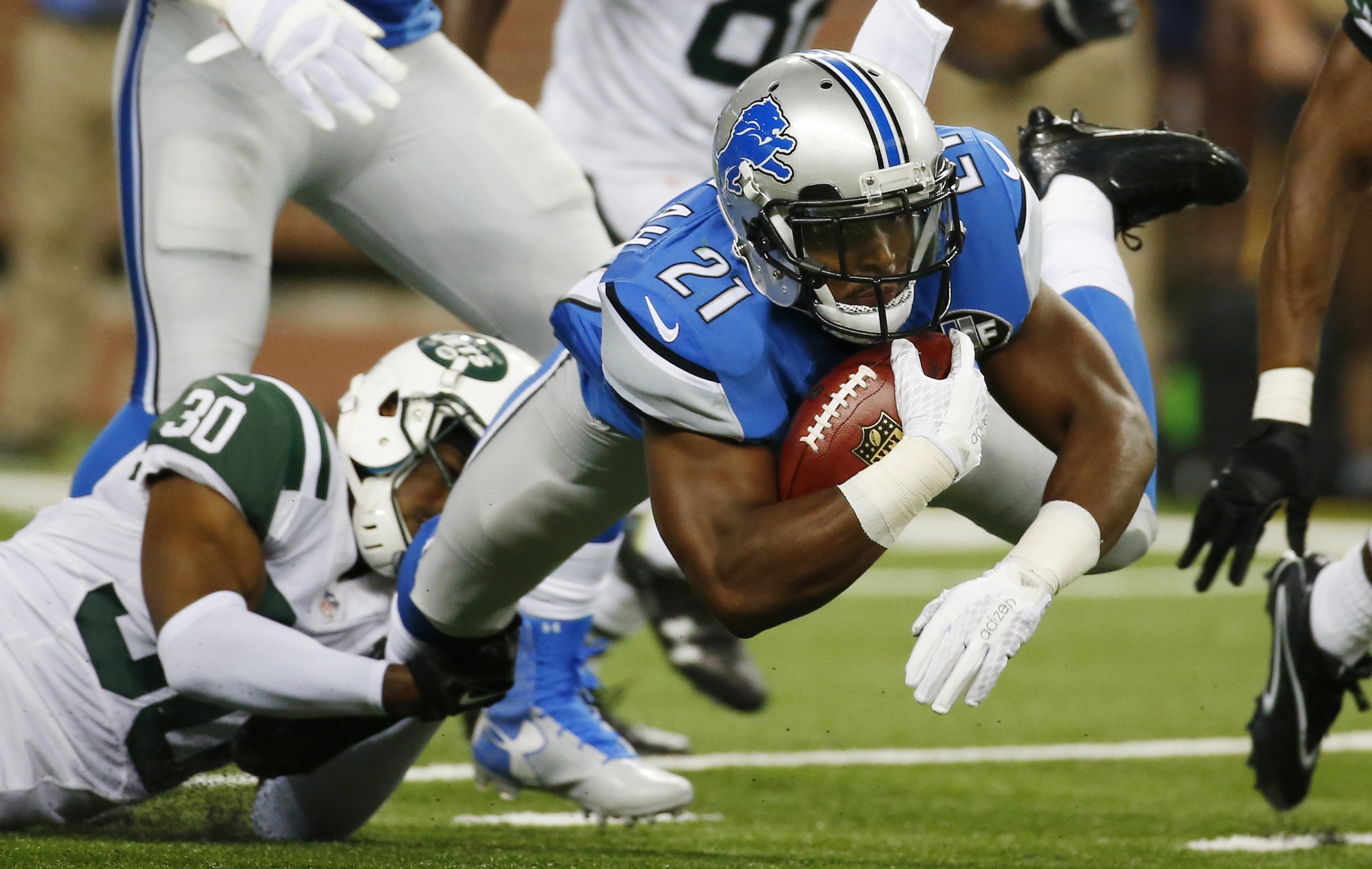 Detroit Lions running back Ameer Abdullah (21) is stopped by New York Jets cornerback Darrin Walls (30) during the first half of an NFL preseason football game, Thursday, Aug. 13, 2015, in Detroit. (AP Photo/Paul Sancya)