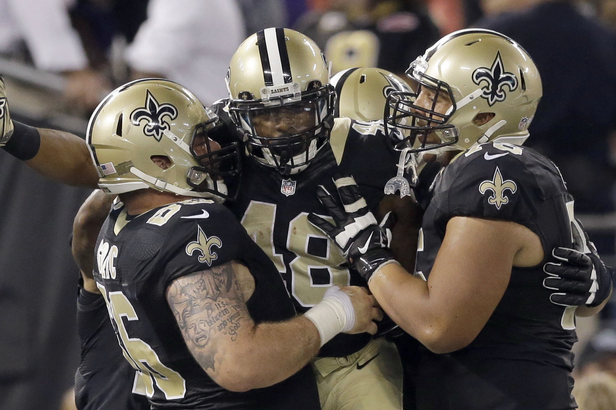 New Orleans Saints running back Marcus Murphy, center, is congratulated by teammates Mike Golic Jr., left, and offensive tackle Andrus Peat, right, after scoring a touchdown during the second half of an NFL preseason football game against the Baltimore Ra
