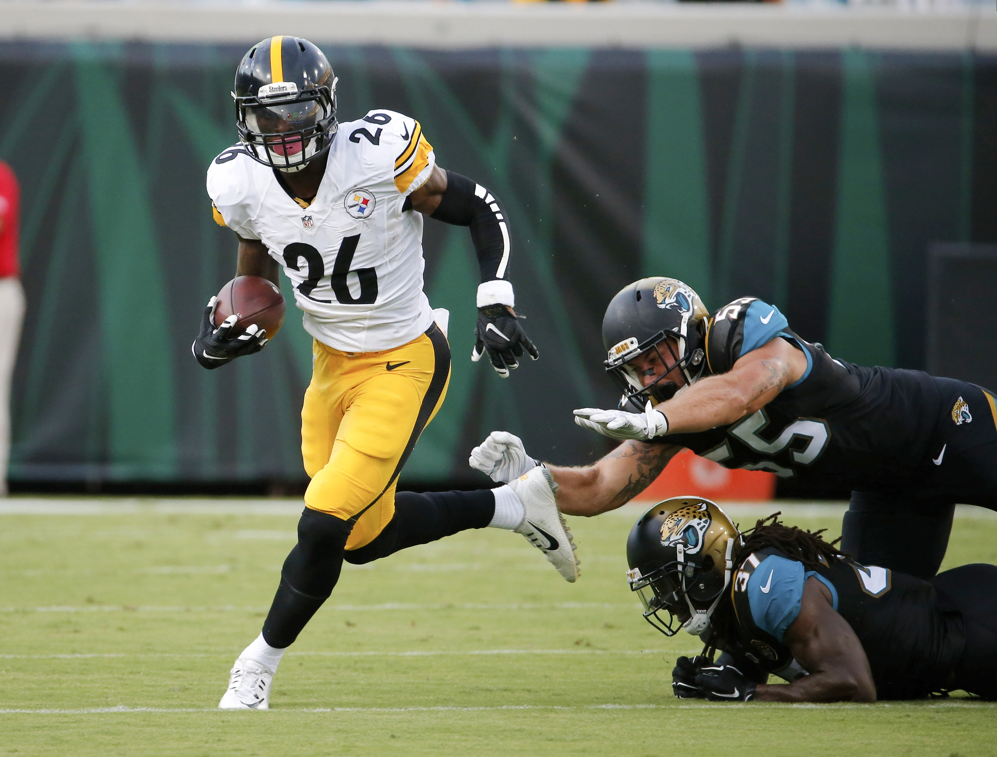 Pittsburgh Steelers running back Le'Veon Bell (26) runs past Jacksonville Jaguars linebacker Dan Skuta, top right, and strong safety Johnathan Cyprien (37) during the first half of an NFL preseason football game, Friday, Aug. 14, 2015, in Jacksonville, Fl
