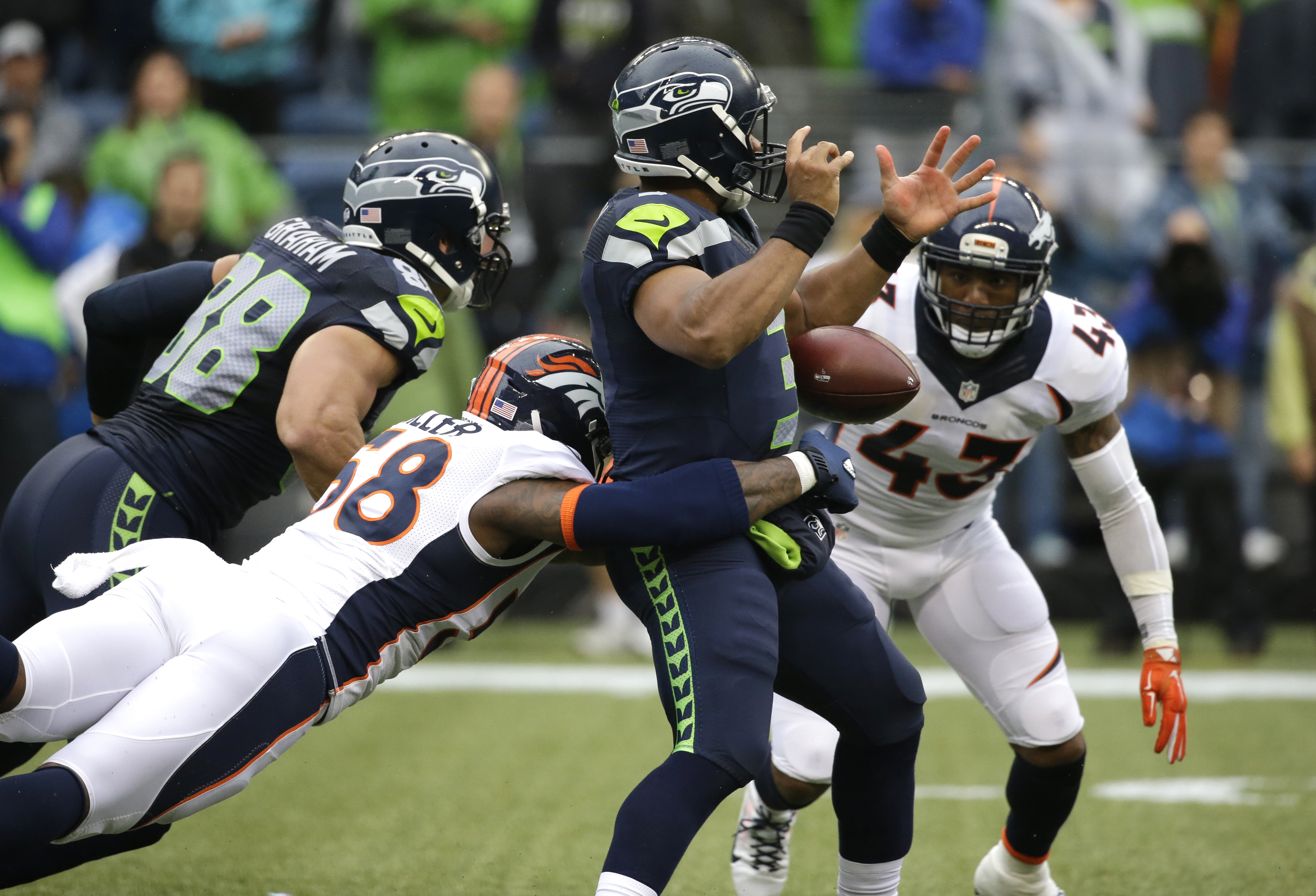 Seattle Seahawks quarterback Russell Wilson has the football stripped by outside linebacker Von Miller, lower left, for a fumble in the first half of a preseason NFL football game, Friday, Aug. 14, 2015, in Seattle. Denver recovered the ball. (AP Photo/El