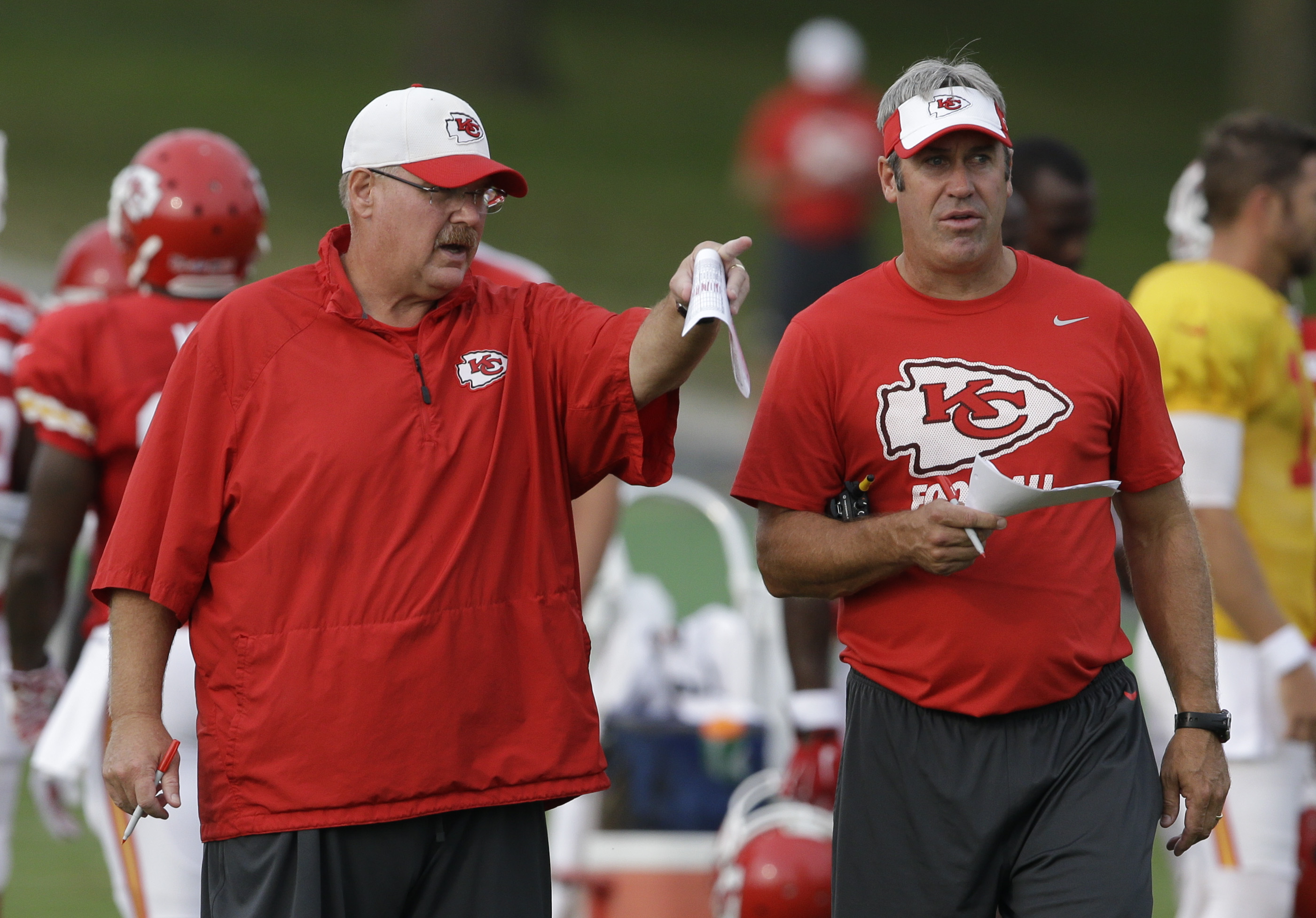 Kansas City Chiefs head coach Andy Reid, left, and offensive coordinator Doug Pederson, right, talk during NFL football training camp in St. Joseph, Mo., Monday, Aug. 17, 2015. (AP Photo/Orlin Wagner)
