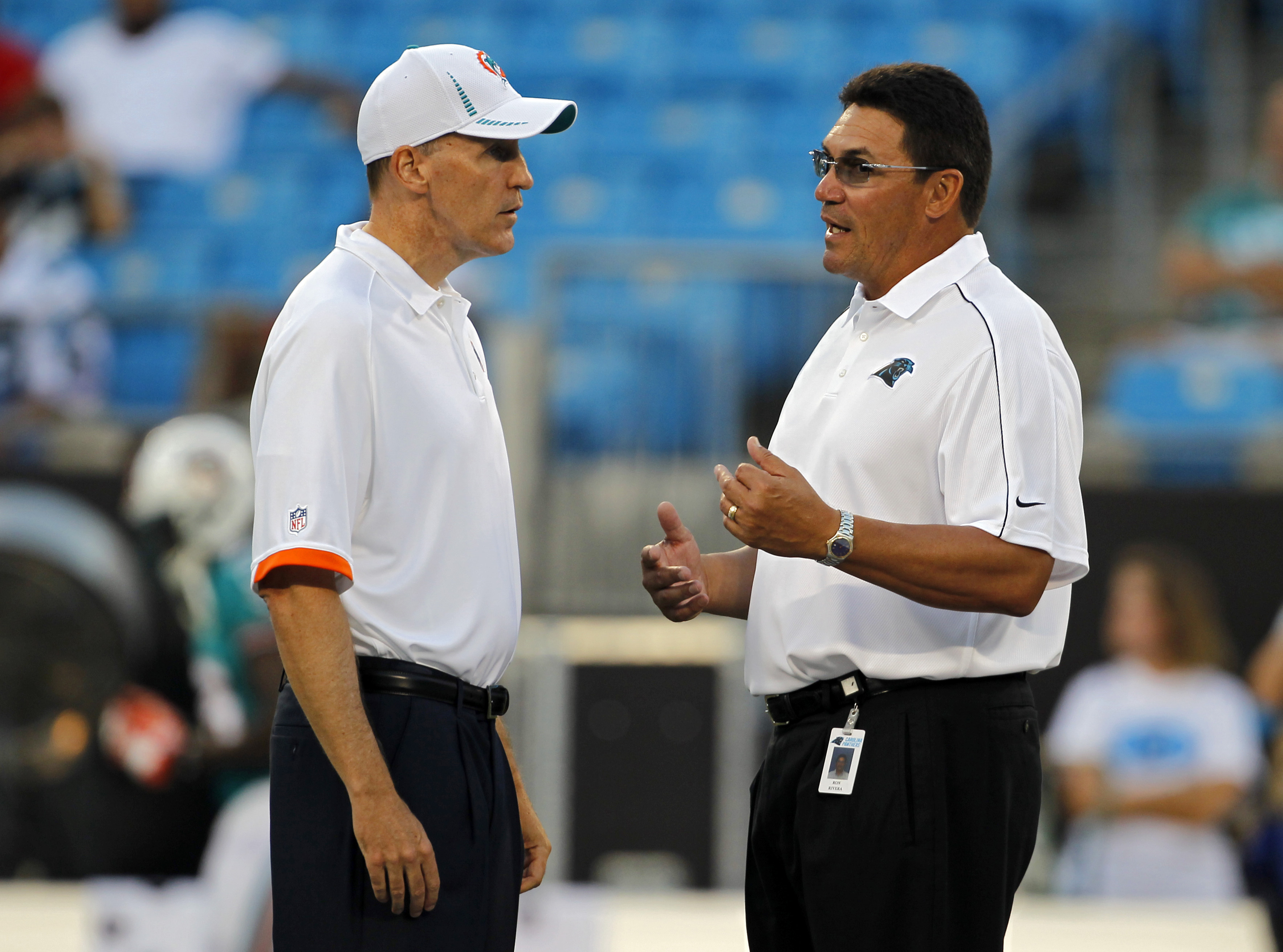 FILE - In this Aug. 17, 2012, file photo, Carolina Panthers head coach Ron Rivera, right, talks with Miami Dolphins head coach Joe Philbin, left, before a preseason NFL football game in Charlotte, N.C. Panthers coach Ron Rivera says he and Dolphins coach