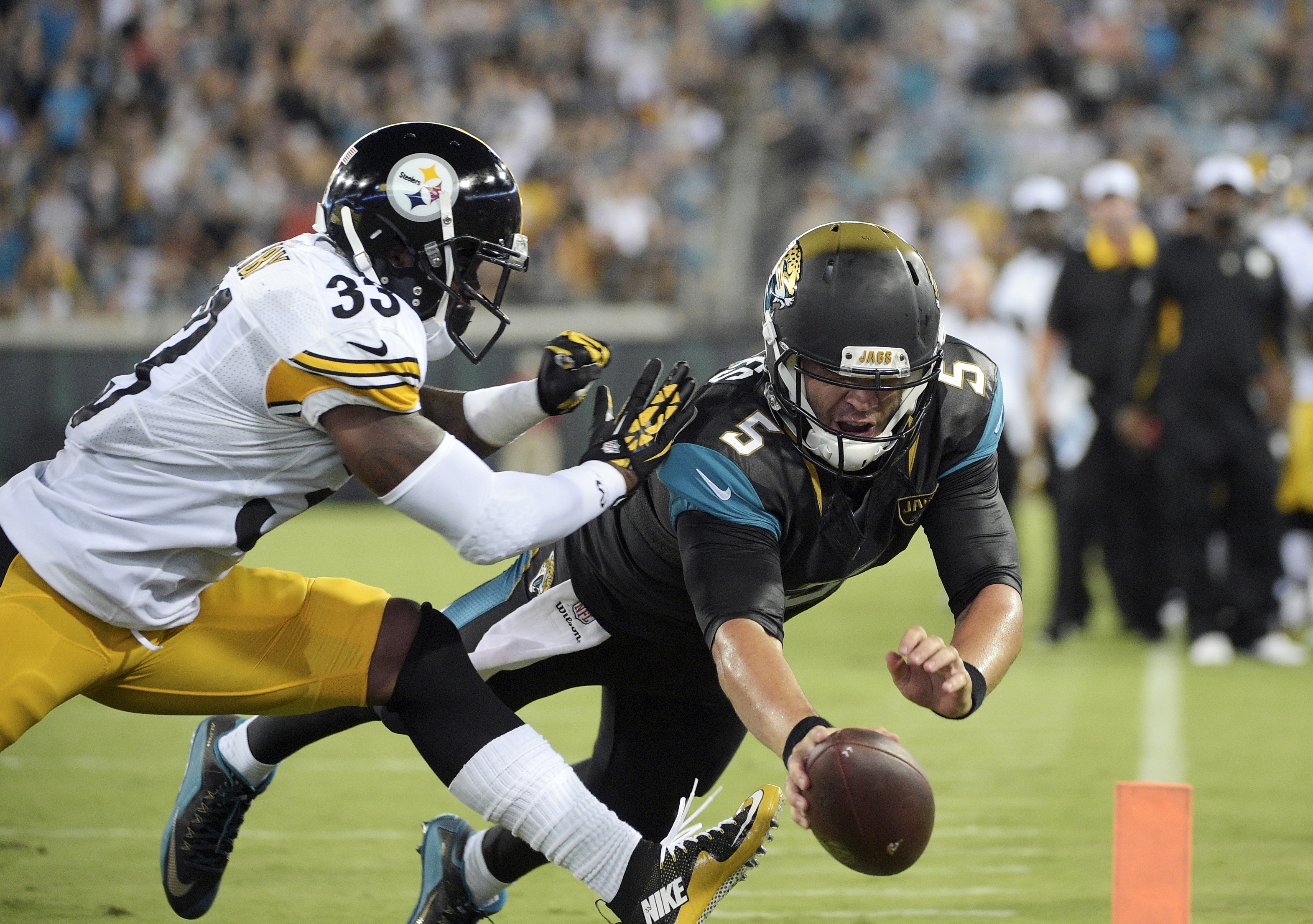 FILE - In this Aug. 14, 2015, file photo, Jacksonville Jaguars quarterback Blake Bortles dives over the goal for a 4-yard touchdown run past Pittsburgh Steelers defensive back Alden Darby (33) during the first half of a preseason NFL football game in Jack