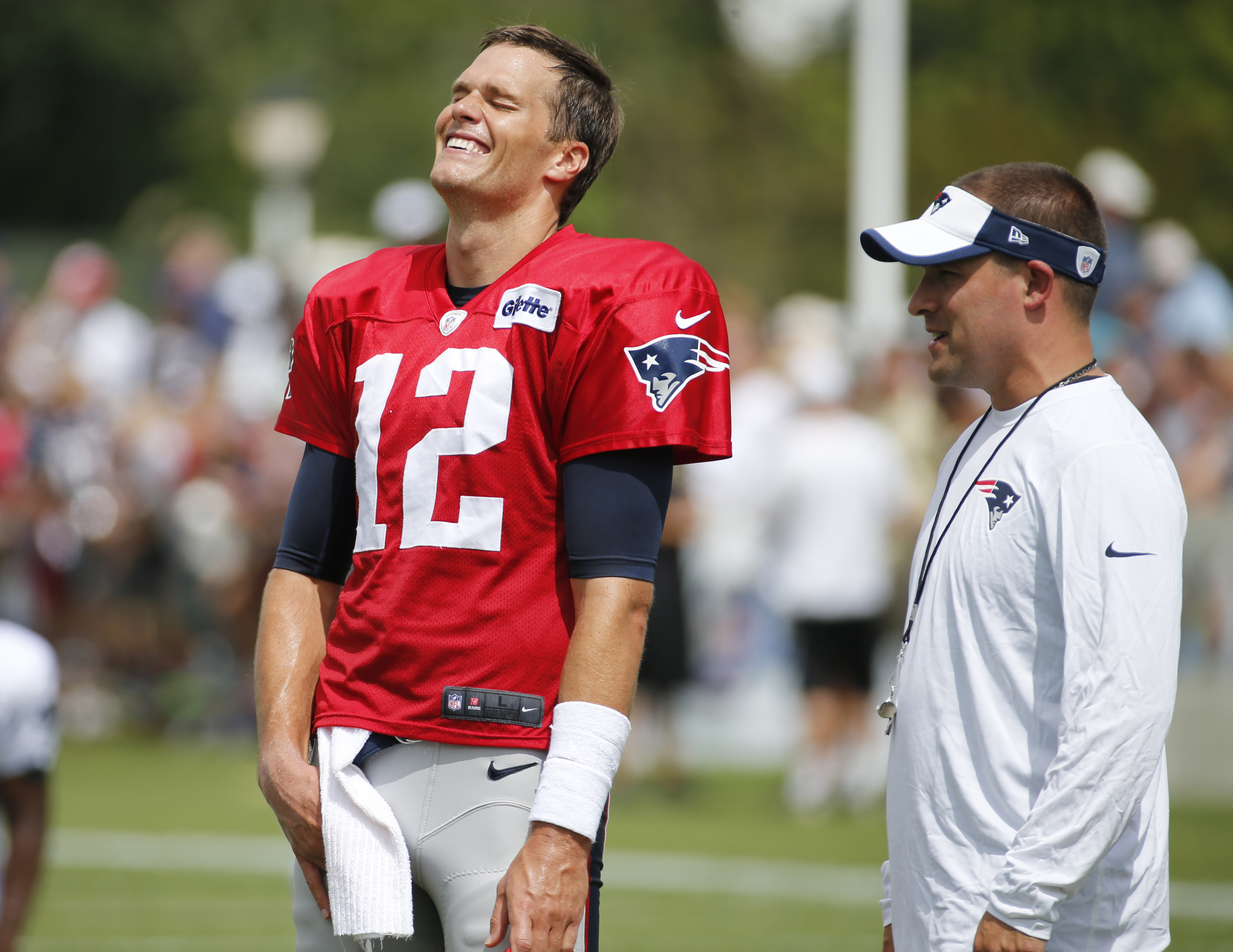 New England Patriot quarterback Tom Brady (12) shares a laugh with offensive coordinator Josh McDaniels during a joint practice between the Patriots and New Orleans Saints at the Saint's NFL football training camp, Wednesday, Aug.19, 2015, in White Sulphu