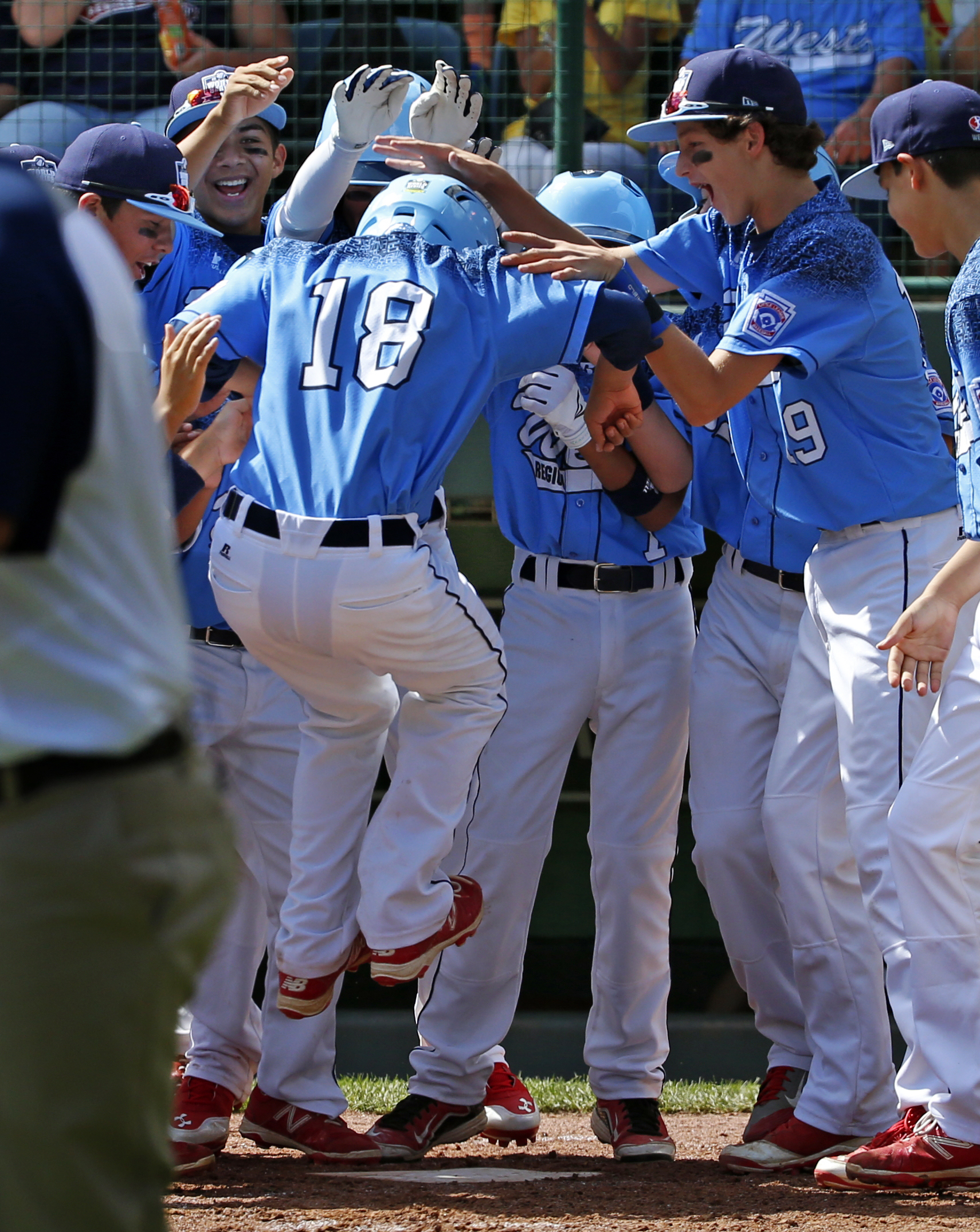 Bonita, California's Nick Maldonado (18) leaps on home plate as he is swarmed by teammates after hitting a grand slam off Bowling Green, Kentucky's Ty Bryant during the third inning of a baseball game in United States pool play at the Little League World