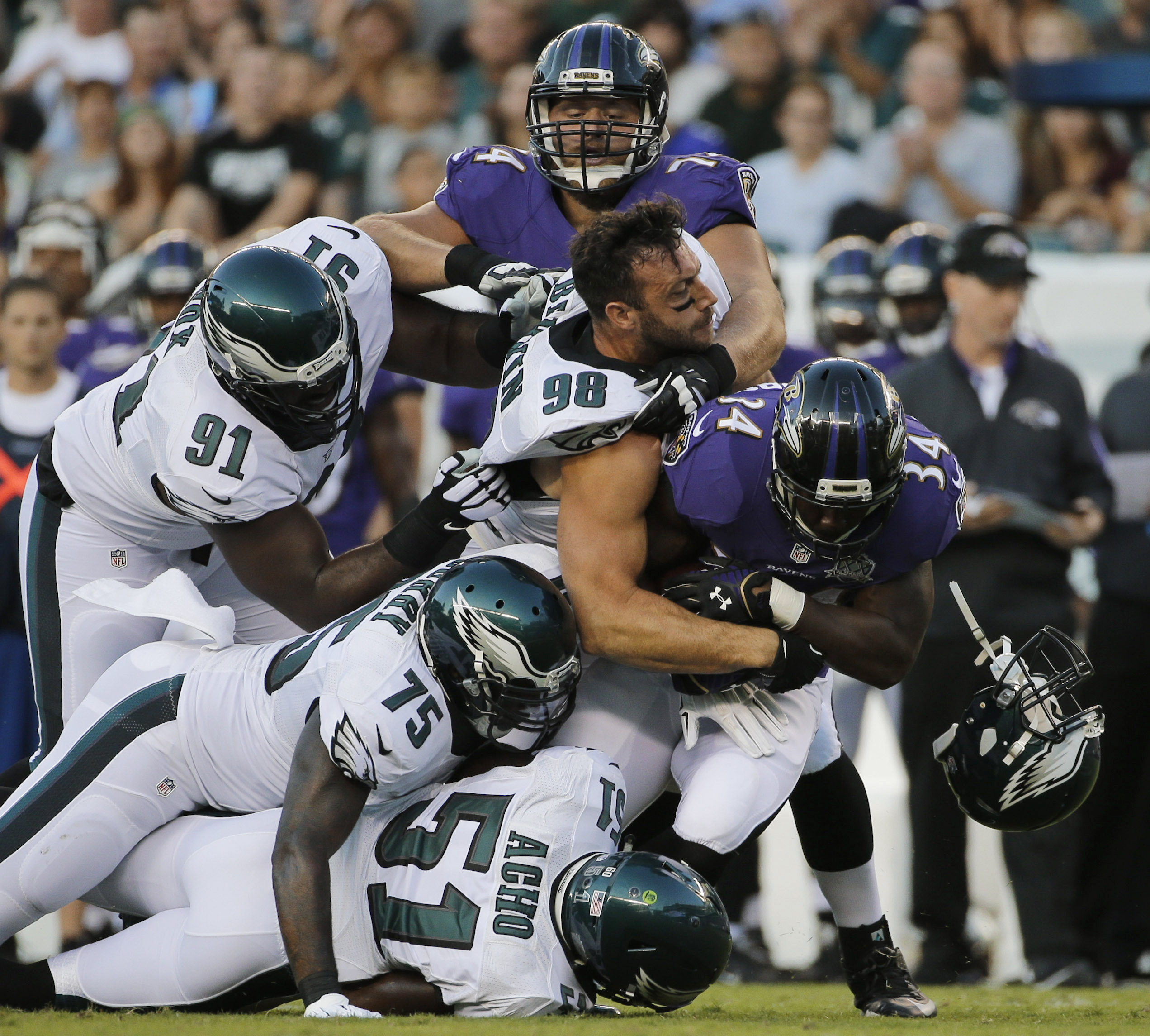 Philadelphia Eagles' Connor Barwin (98) loses his helmet as he combines with Emmanuel Acho (51), Vinny Curry (75) and Fletcher Cox (91) to tackle Baltimore Ravens' Lorenzo Taliaferro (34) during the first half of a preseason NFL football game, Saturday, A