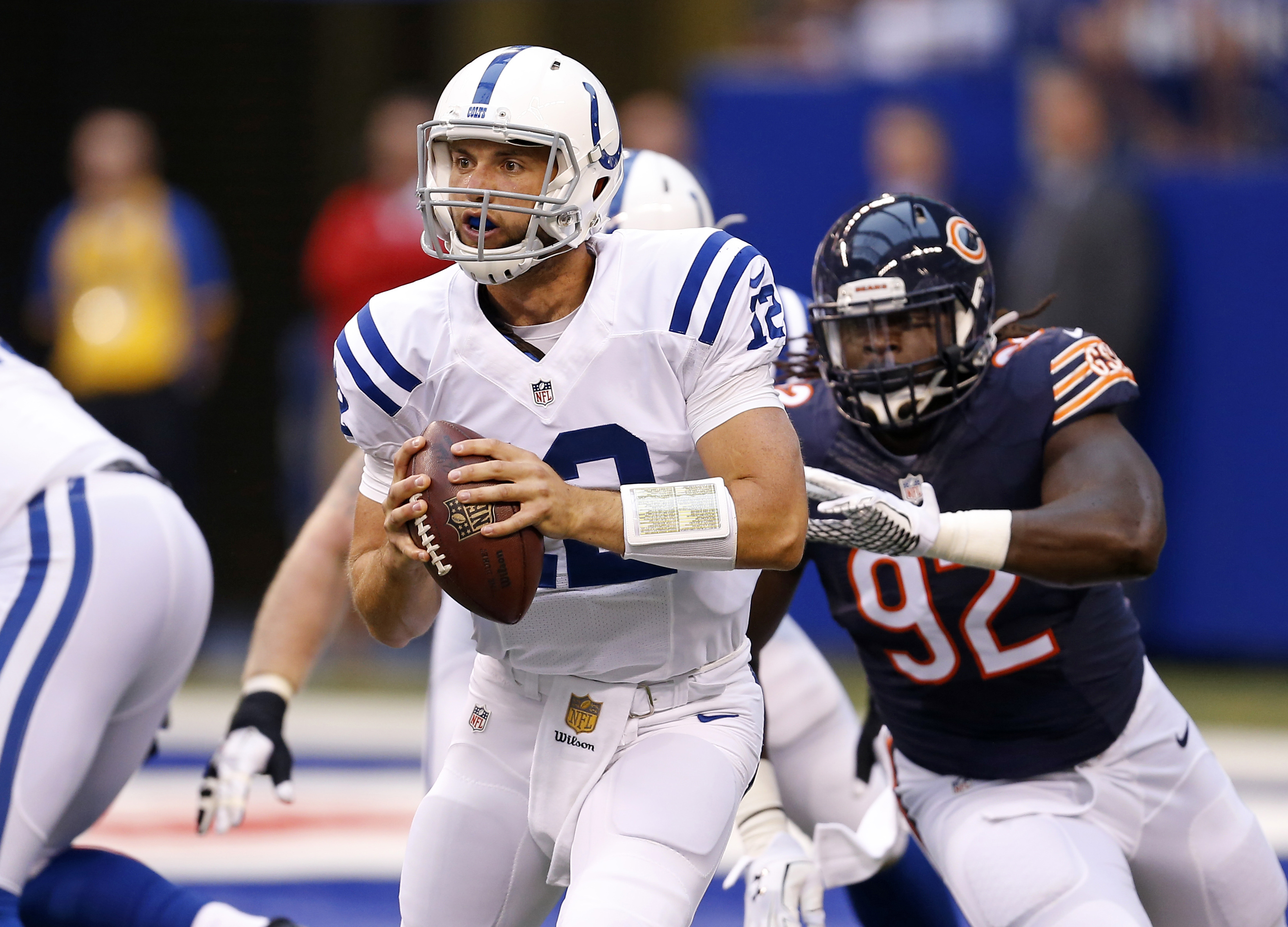 Indianapolis Colts quarterback Andrew Luck (12) is chased by Chicago Bears defensive end Pernell McPhee (92) during the first half of an NFL preseason football game in Indianapolis, Saturday, Aug. 22, 2015.  (AP Photo/Sam Riche)