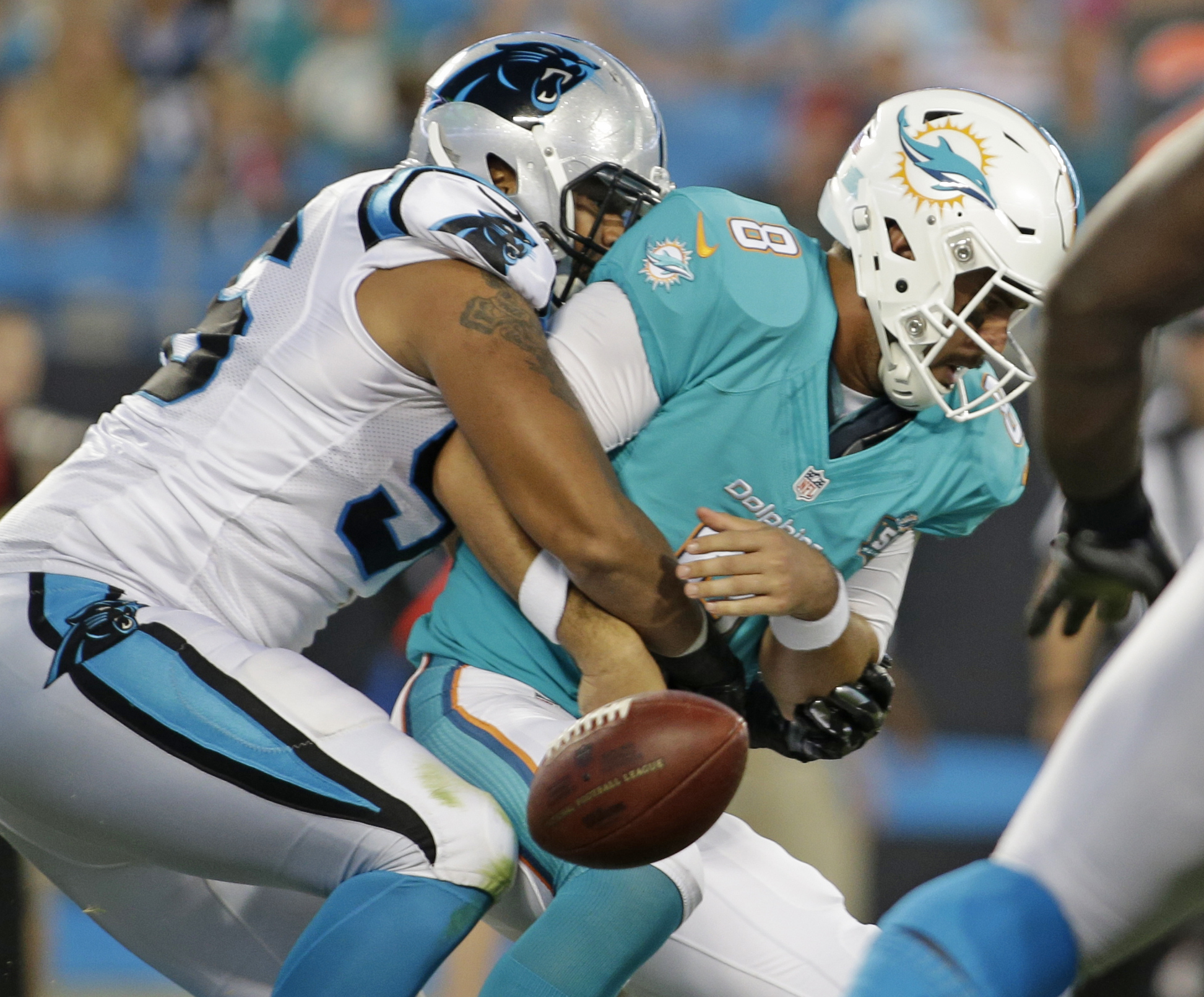 Miami Dolphins' Matt Moore (8) fumbles the ball after being hit by Carolina Panthers' Wes Horton (96) during the first half of an NFL preseason football game in Charlotte, N.C., Saturday, Aug. 22, 2015. The Dolphins recovered the ball. (AP Photo/Bob Lever