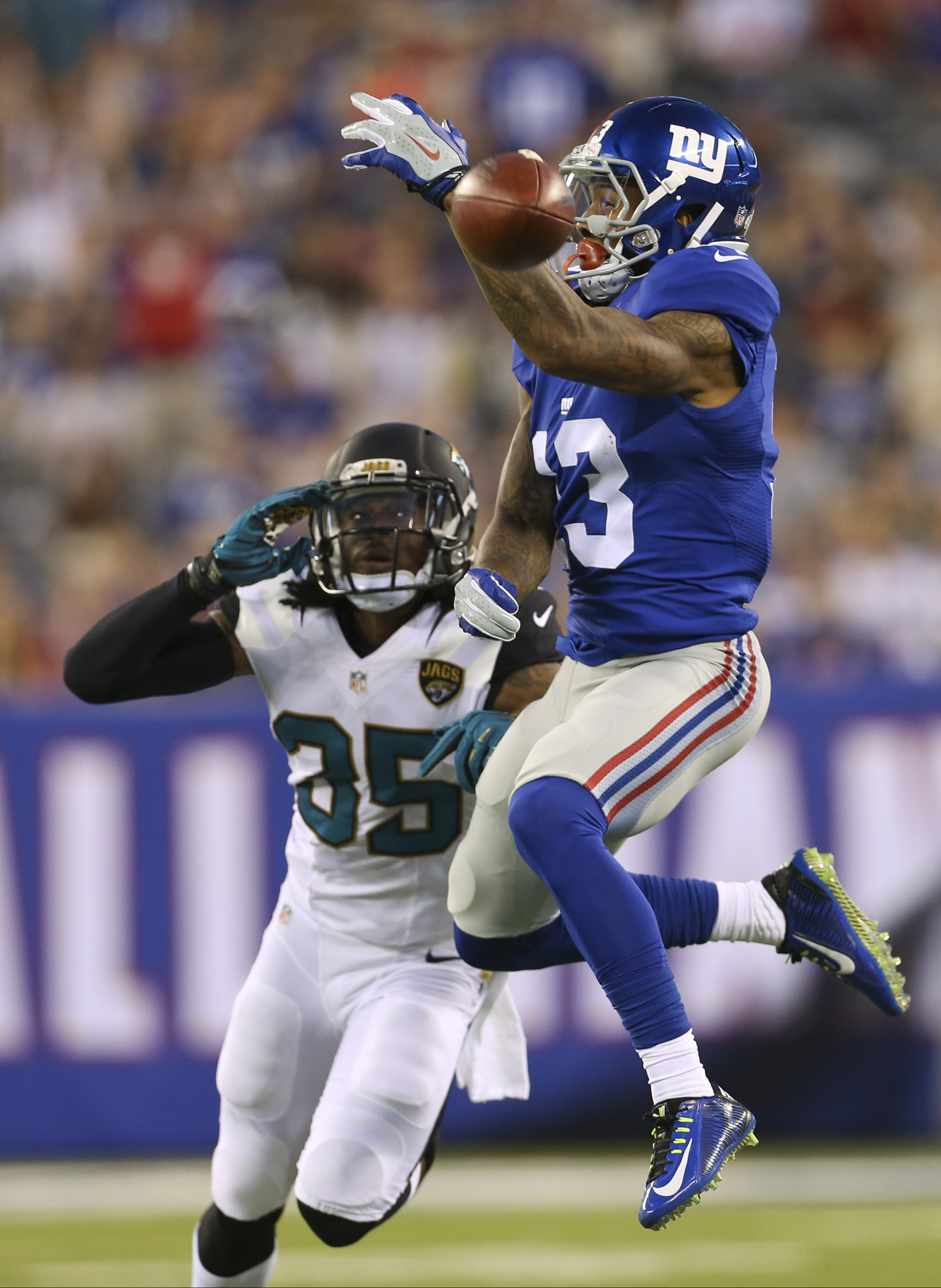 New York Giants wide receiver Odell Beckham (13) leaps for a ball thrown by quarterback Eli Manning as Jacksonville Jaguars' Demetrius McCray (35) watches during the first half of a preseason NFL football game Saturday, Aug. 22, 2015, in East Rutherford,