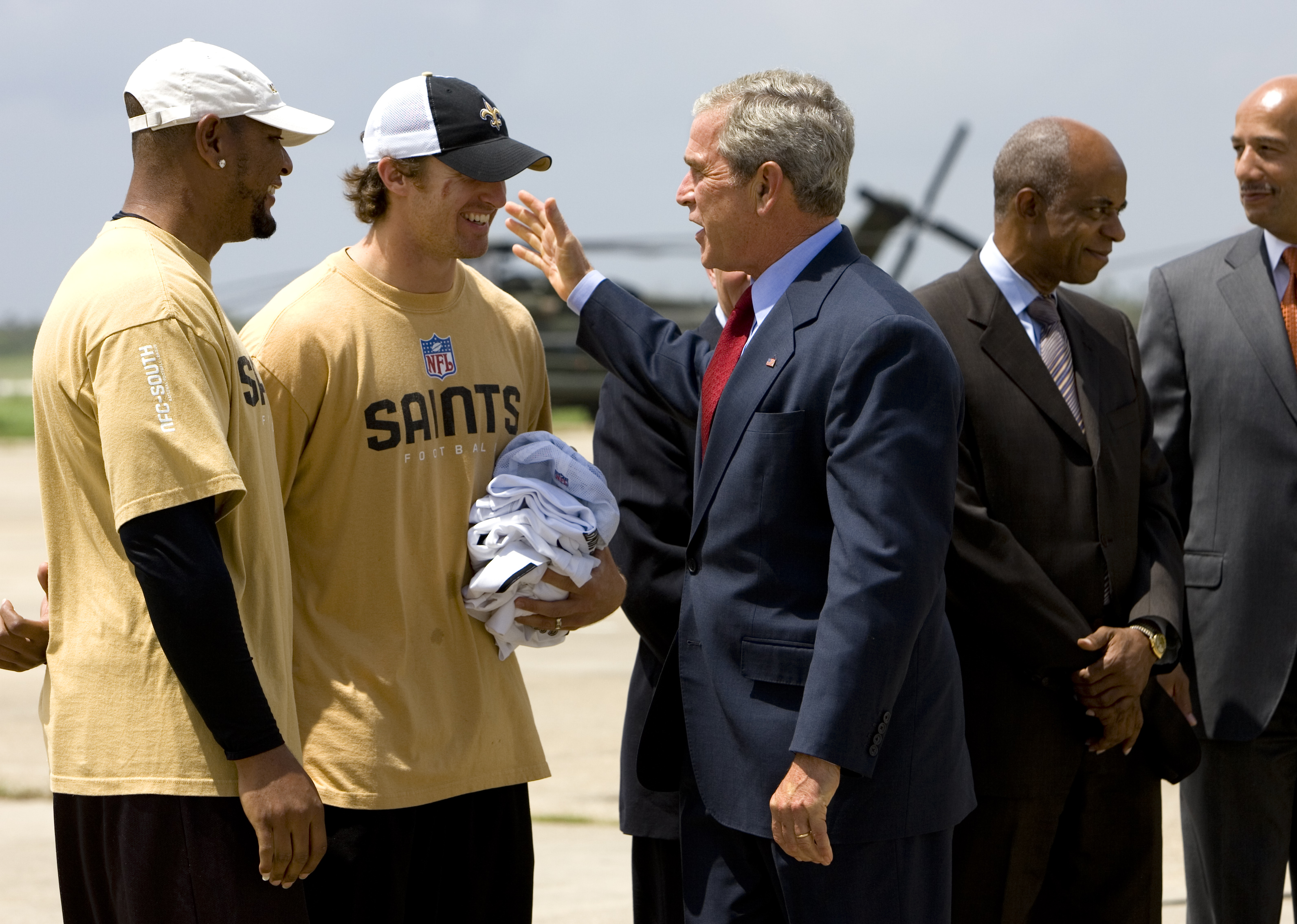 FILE - In this Aug. 8, 2008, file photo, President George W. Bush is met by Deuce McAllister, left, and Drew Brees of the New Orleans Saints football team as he arrives at Louis Armstrong New Orleans International Airport on the way to events marking the