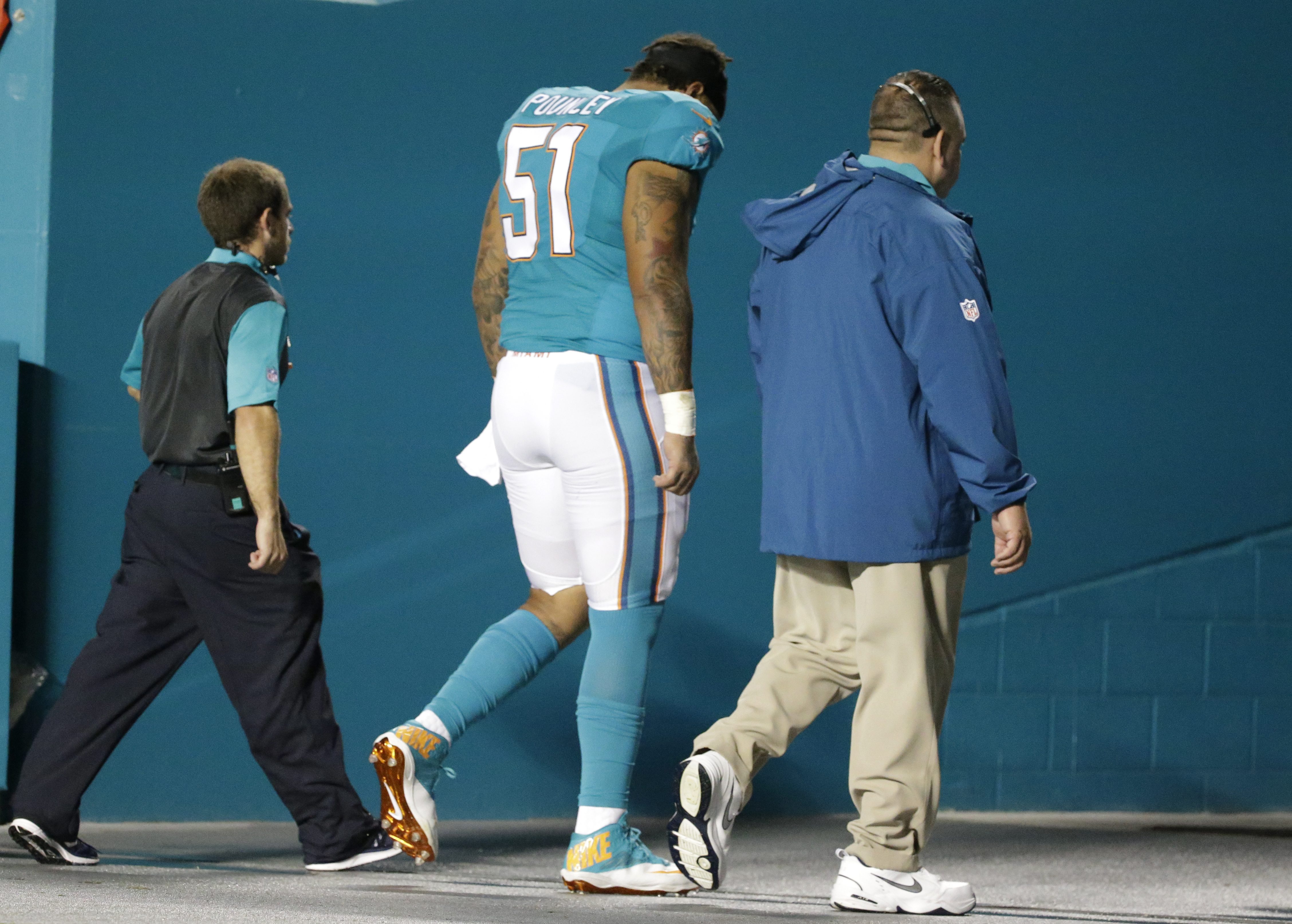 Miami Dolphins guard Mike Pouncey (51) is lead off the field during the first half of an NFL preseason football game against the Atlanta Falcons, Saturday, Aug. 29, 2015 in Miami Gardens, Fla. (AP Photo/Wilfredo Lee)