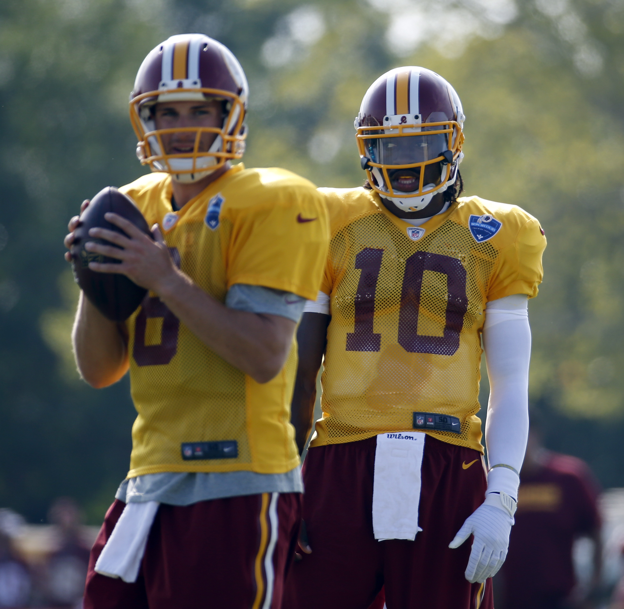 FILE - In this July 26, 2014, file photo, Washington Redskins quarterback Kirk Cousins prepares to pass as quarterback Robert Griffin III watches during practice at the team's NFL football training facility in Richmond, Va. The Washington Redskins have ma