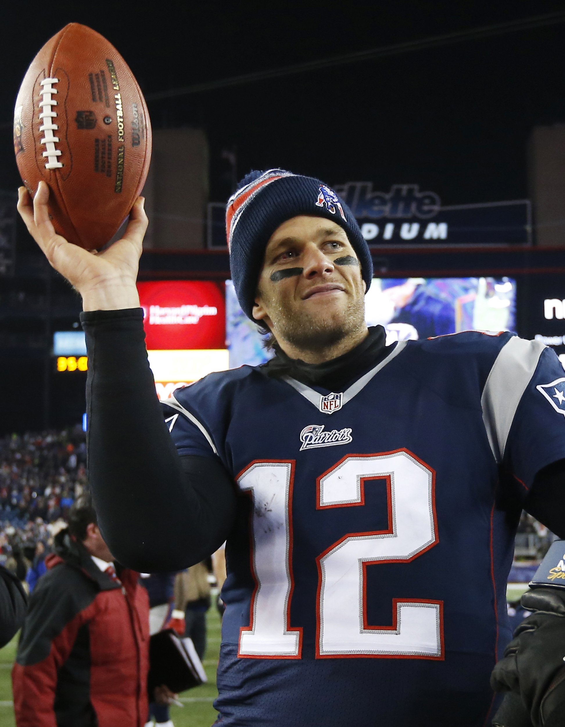 FILE - In this Jan. 10, 2015, file photo, New England Patriots quarterback Tom Brady holds up the game ball after an NFL divisional playoff football game against the Baltimore Ravens in Foxborough, Mass. Brady can suit up for his team's season opener afte