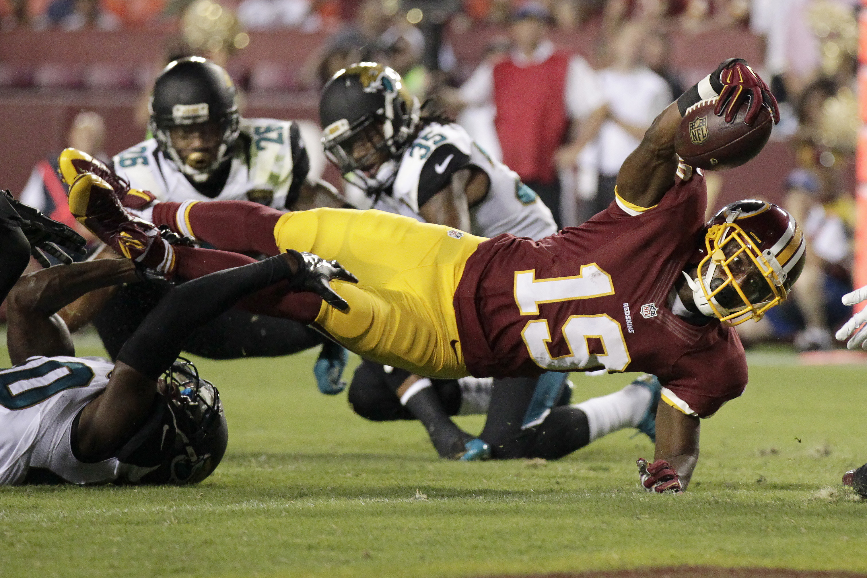 Washington Redskins wide receiver Rashad Ross (19) reaches into the end zone for a touchdown as Jacksonville Jaguars cornerback Rashaad Reynolds (40) hangs on during the first half of an NFL preseason football game in Landover, Md., Thursday, Sept. 3, 201
