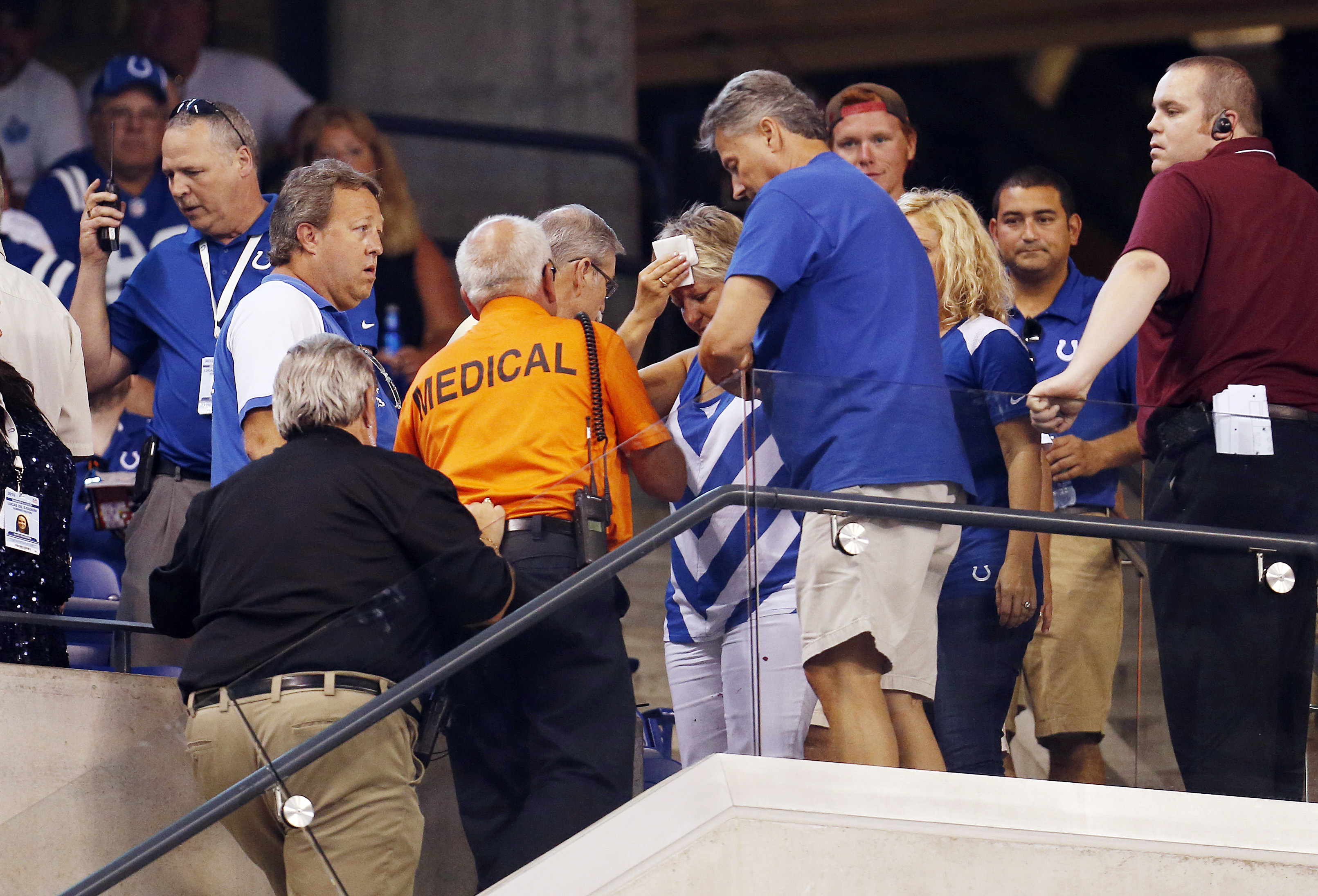 A fan is helped by emergency workers after getting injured by falling debris as the roof was opened during halftime of an NFL preseason football game between the Indianapolis Colts and the Cincinnati Bengals, Thursday, Sept. 3, 2015, in Indianapolis. (AP