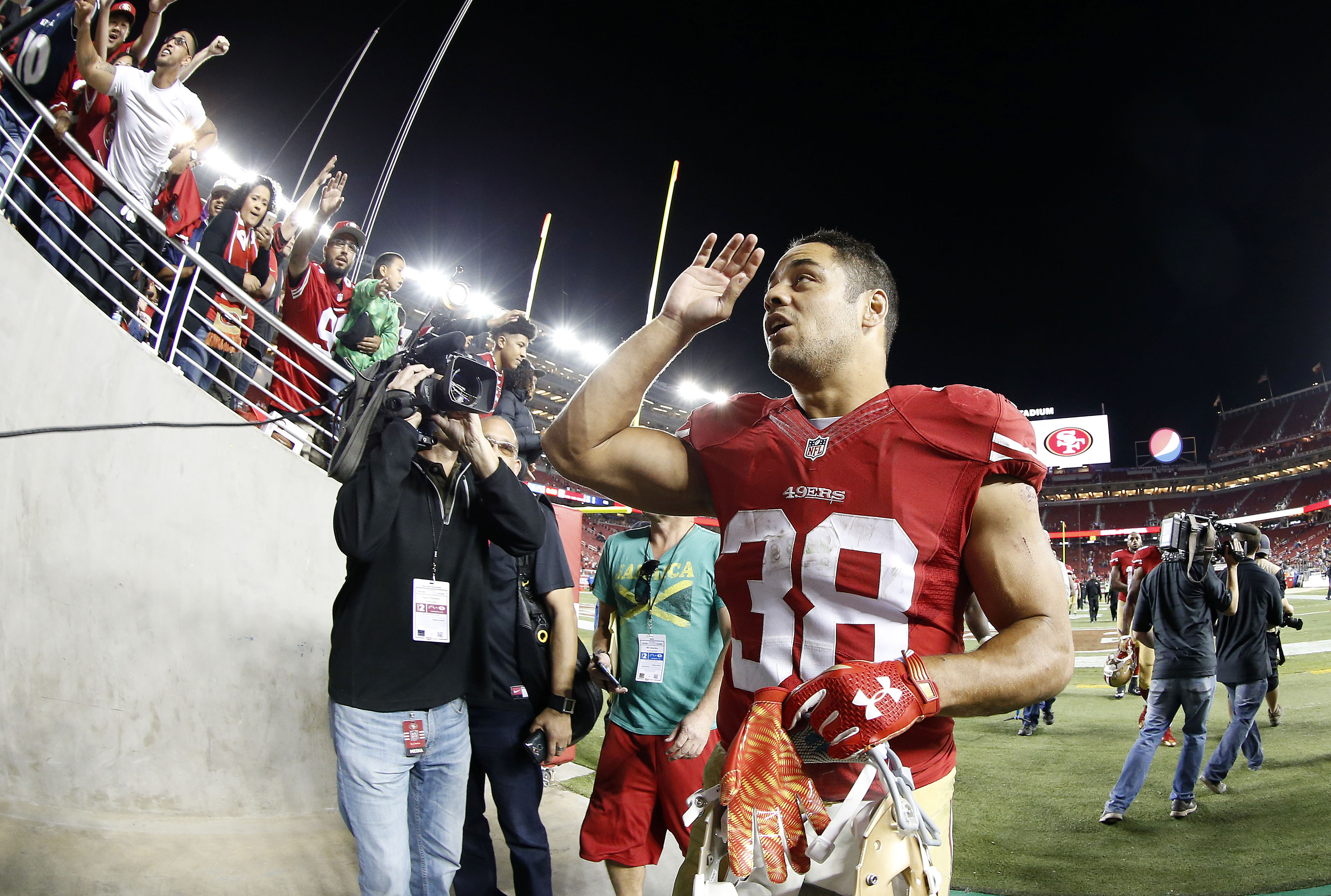 In this photo taken with a fisheye lens, San Francisco 49ers running back Jarryd Hayne (38) waves to fans after an NFL preseason football game against the San Diego Chargers in Santa Clara, Calif., Thursday, Sept. 3, 2015. The 49ers won 14-12. (AP Photo/T