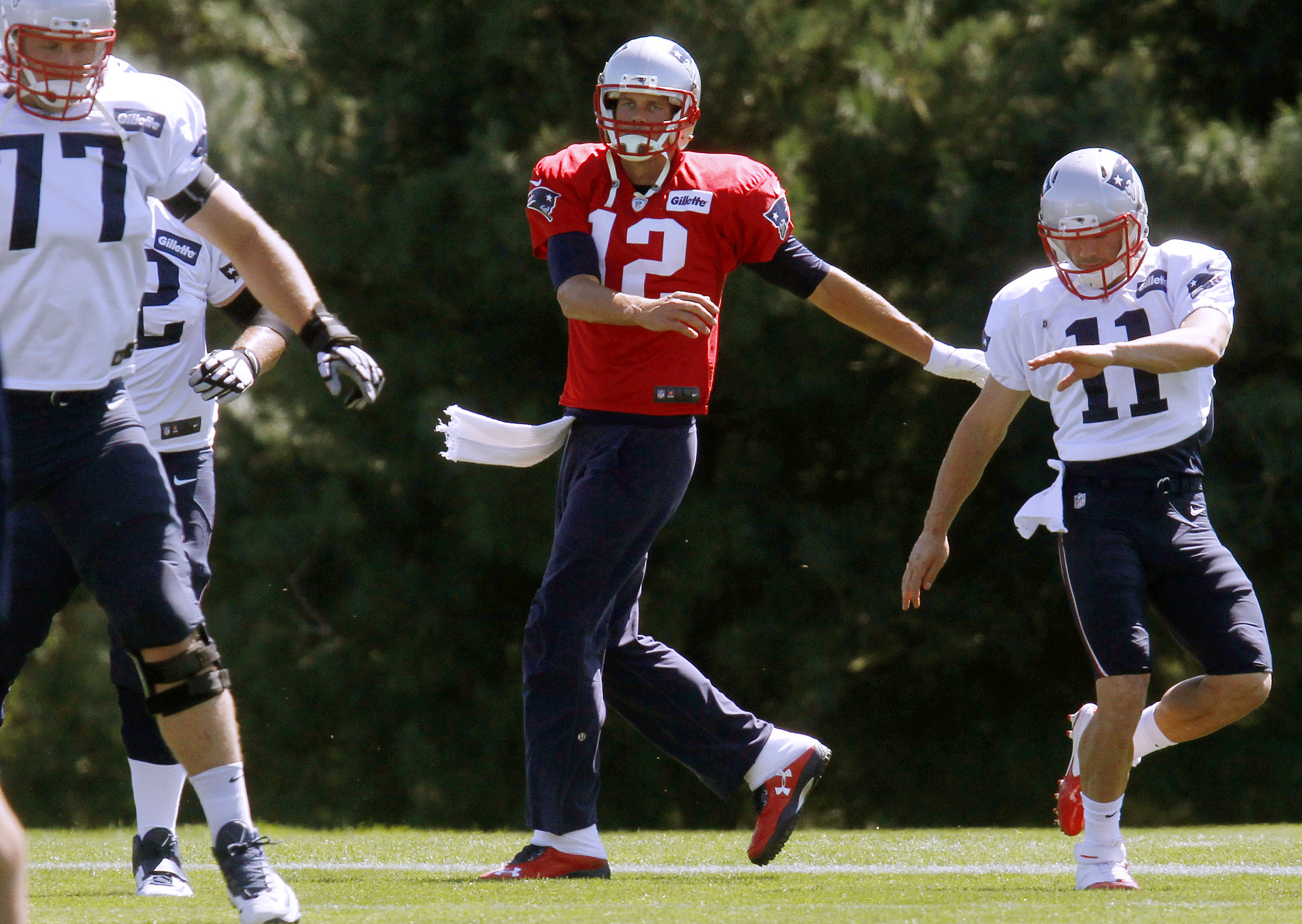 New England Patriots quarterback Tom Brady, center, warms up between tackle Nate Solder, left, and wide receiver Julian Edelman, right, at the beginning of NFL football practice, Saturday, Sept. 5, 2015, in Foxborough, Mass. A federal judge overturned Bra