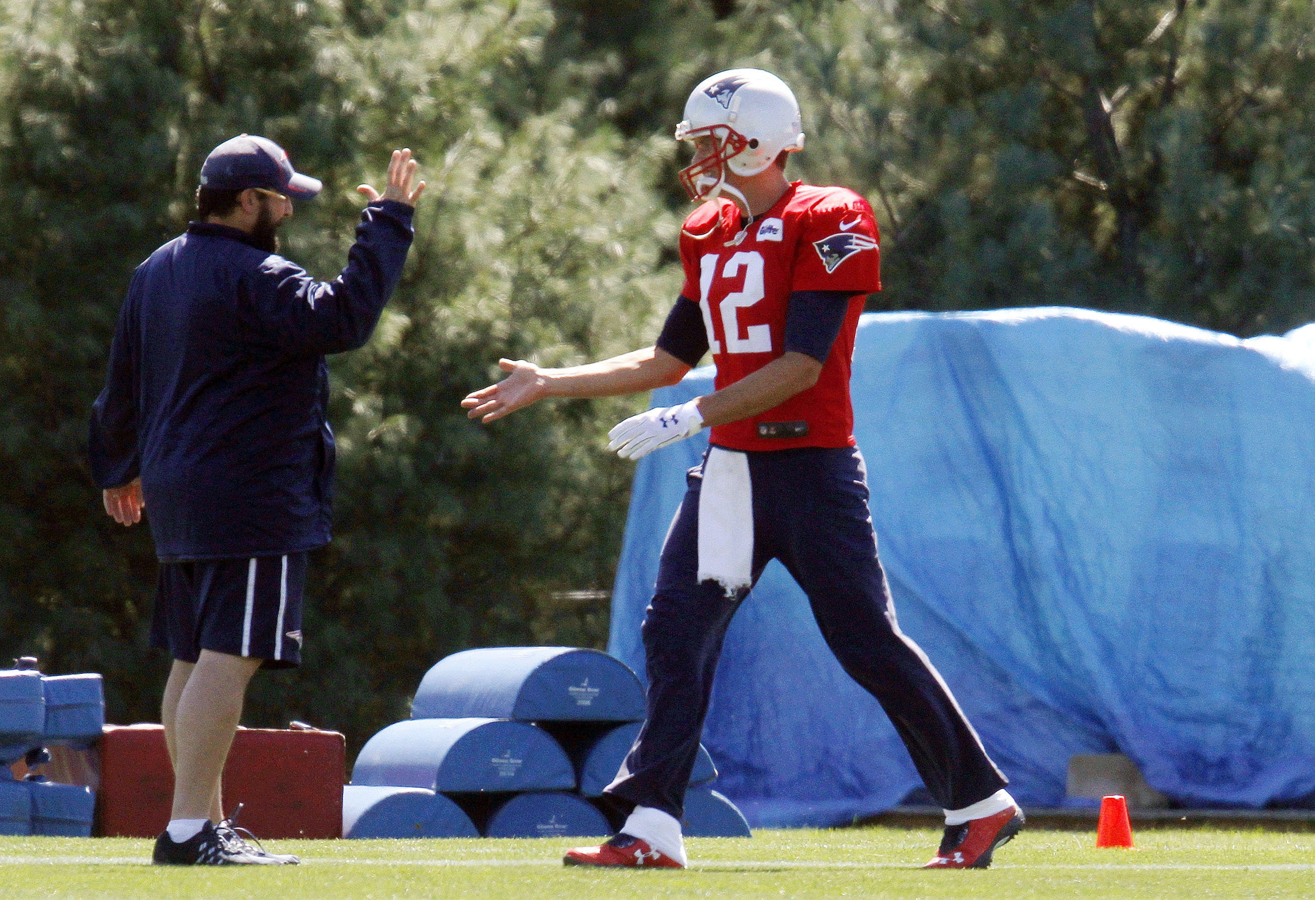 New England Patriots football quarterback Tom Brady (12) greets New England Patriots defensive coordinator Matt Patricia, left, at the start of practice Saturday, Sept. 5, 2015, in Foxborough, Mass. A federal judge overturned Brady's four-game suspension